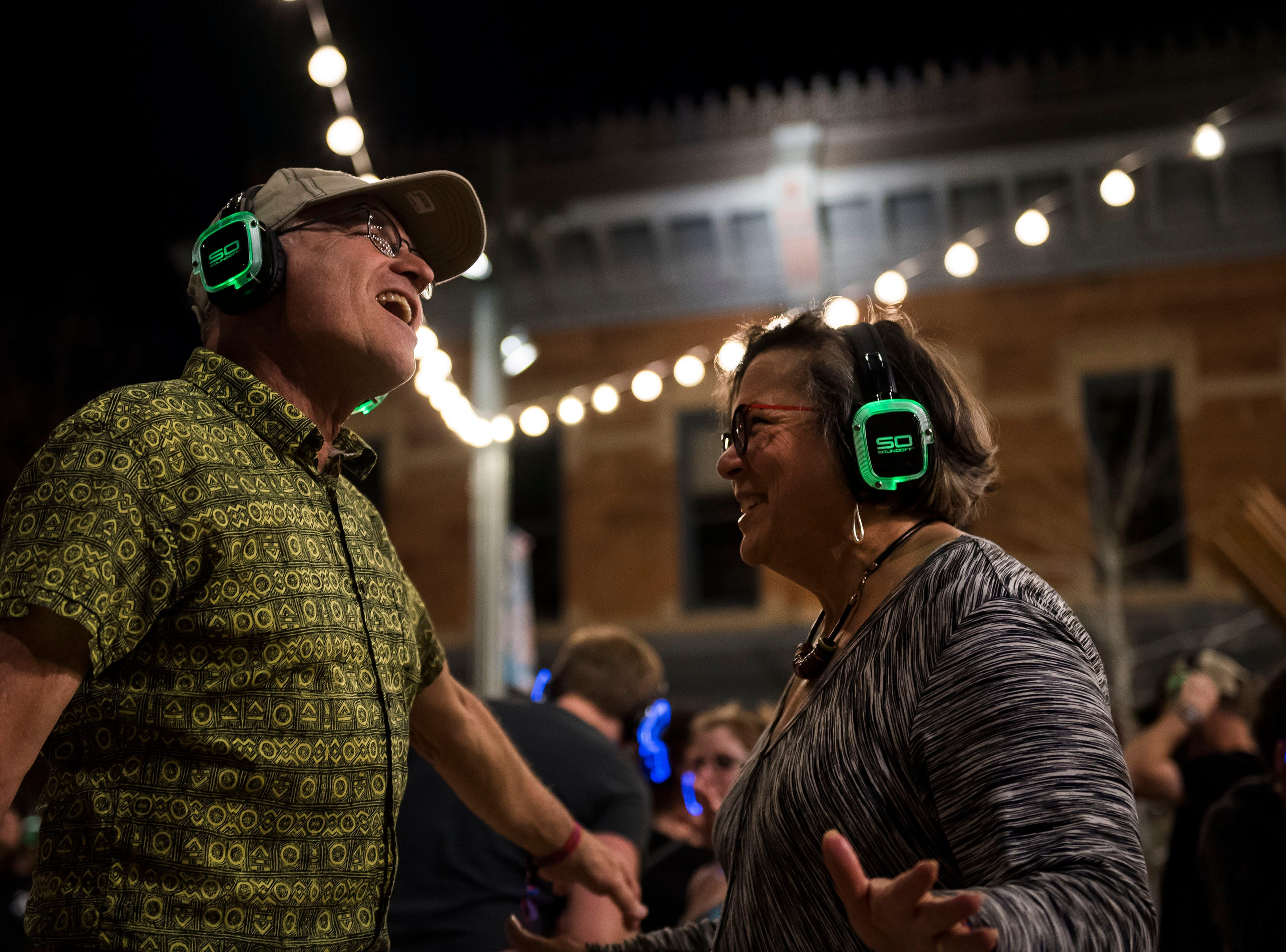 Marge and Willie Portilla listen to DJ Blakeye at the Sound Off Silent Disco at Old Town Square during the FoCoMX XI music festival on Friday, April 26, 2019, in Fort Collins, Colo.