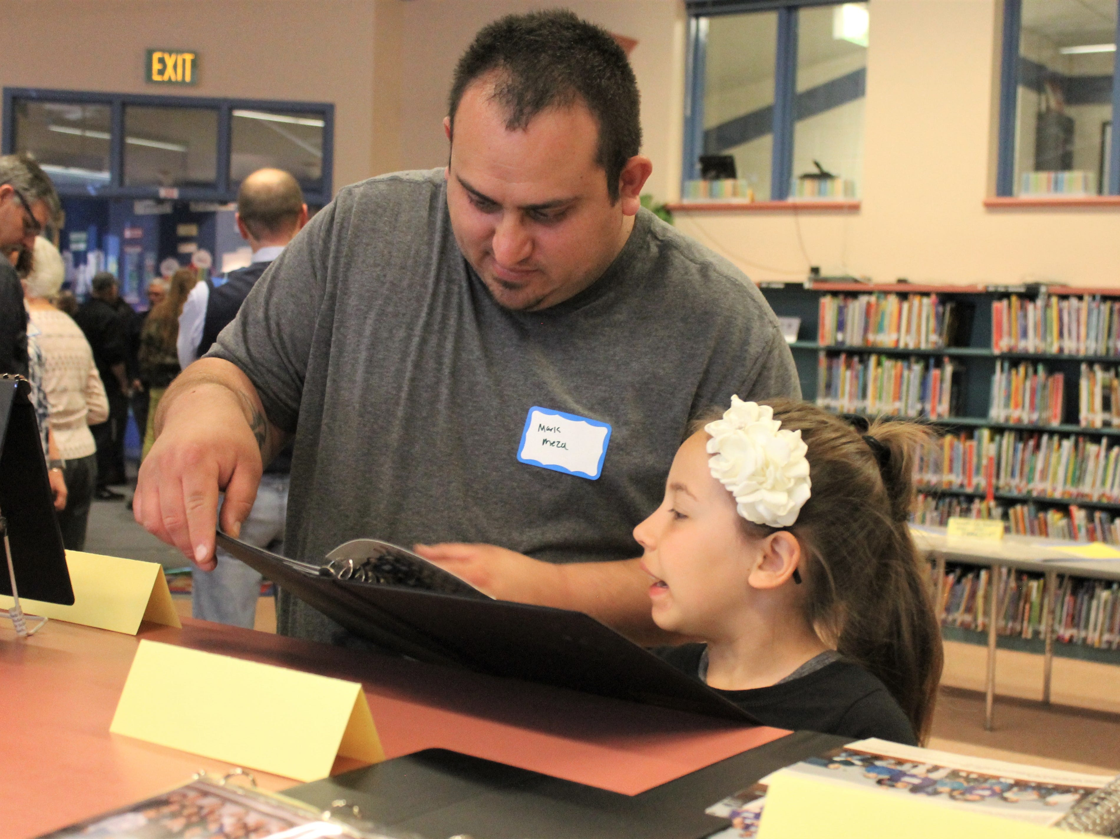 Mark Meza points out old photos of him as a student at Timnath Elementary School to his daughter, Jesselin Stankus, 8. Timnath Elementary School celebrated its 100th anniversary Saturday, April 27, 2019.
