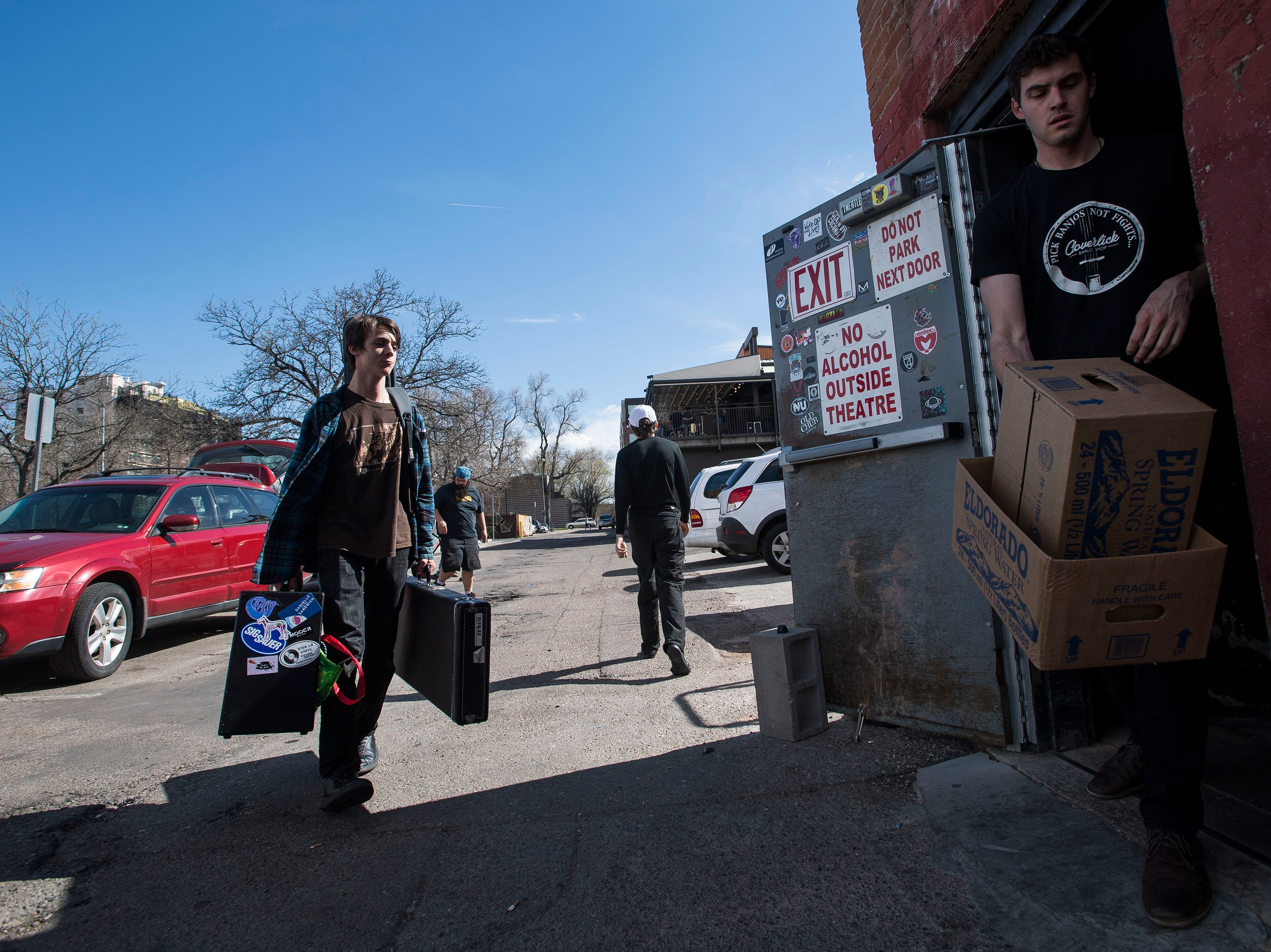 My Dog Ate Chad band member Nico Cutbirth carries a guitar and amp into The Aggie Theatre while production manager Will Reutemann tosses a few boxes out the back door during the FoCoMX XI music festival on Friday, April 26, 2019, in Fort Collins, Colo.