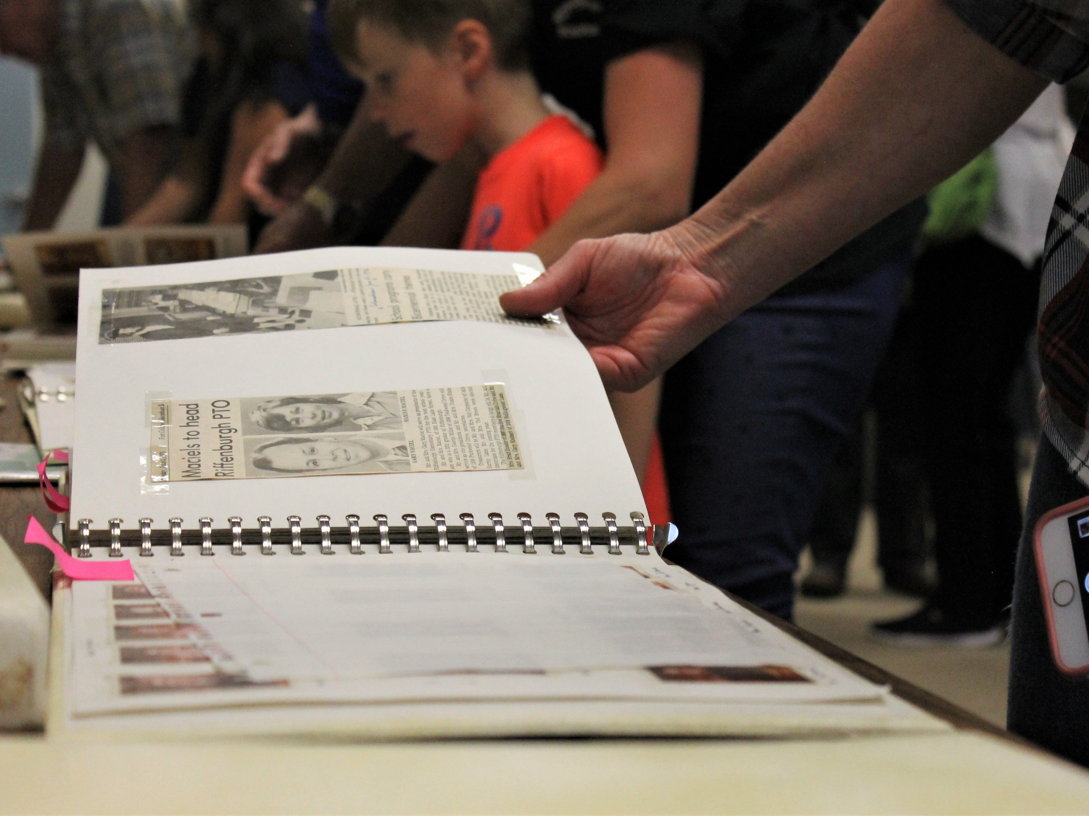 Students, parents and alum flip through old news clippings Friday at Riffenburgh Elementary School's 50th anniversary celebration.