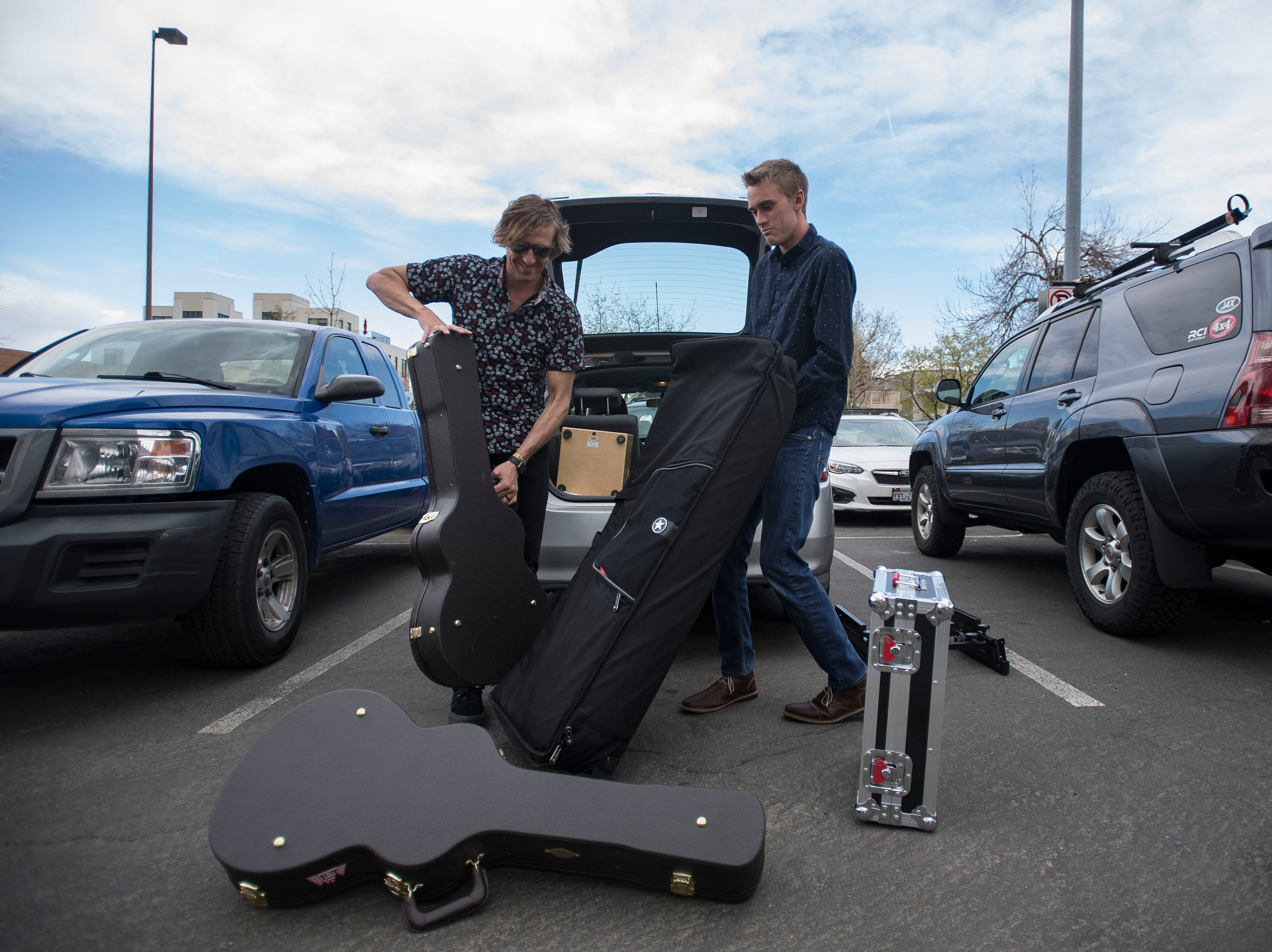 The 14ers members Ryan Kirkpatrick, left, and Jacob Anderson pull instruments out of their car before heading in and setting up at Tony's Bar & Rooftop during the FoCoMX XI music festival on Friday, April 26, 2019, in Fort Collins, Colo.
