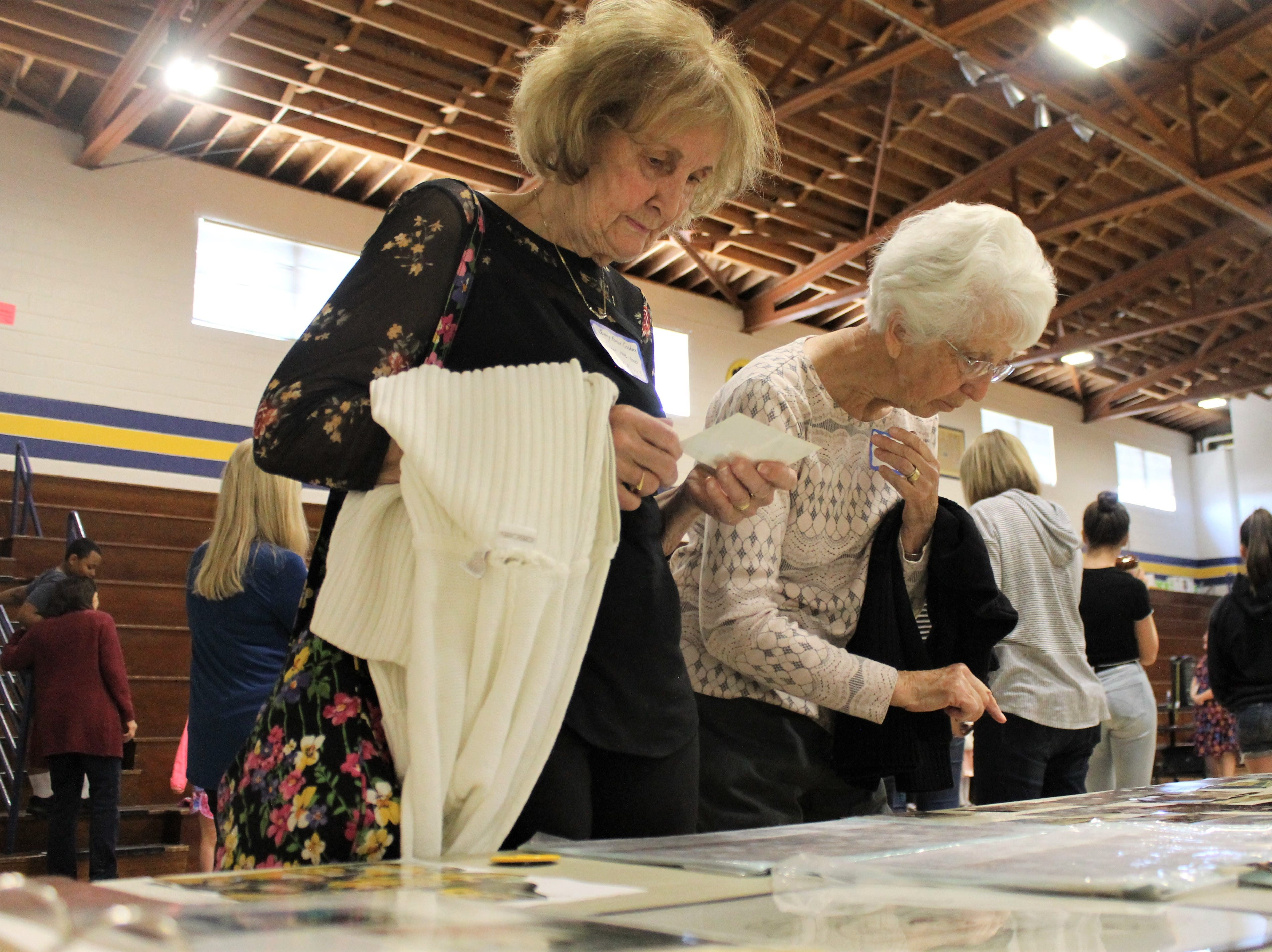 Bunny Roeser Goshorn and Ann Hitchman look through photos at Timnath Elementary School's 100th anniversary celebration Saturday, April 27, 2019. Roeser Goshorn taught at the school from 1976-2000. Hitchman taught from 1982-2000.