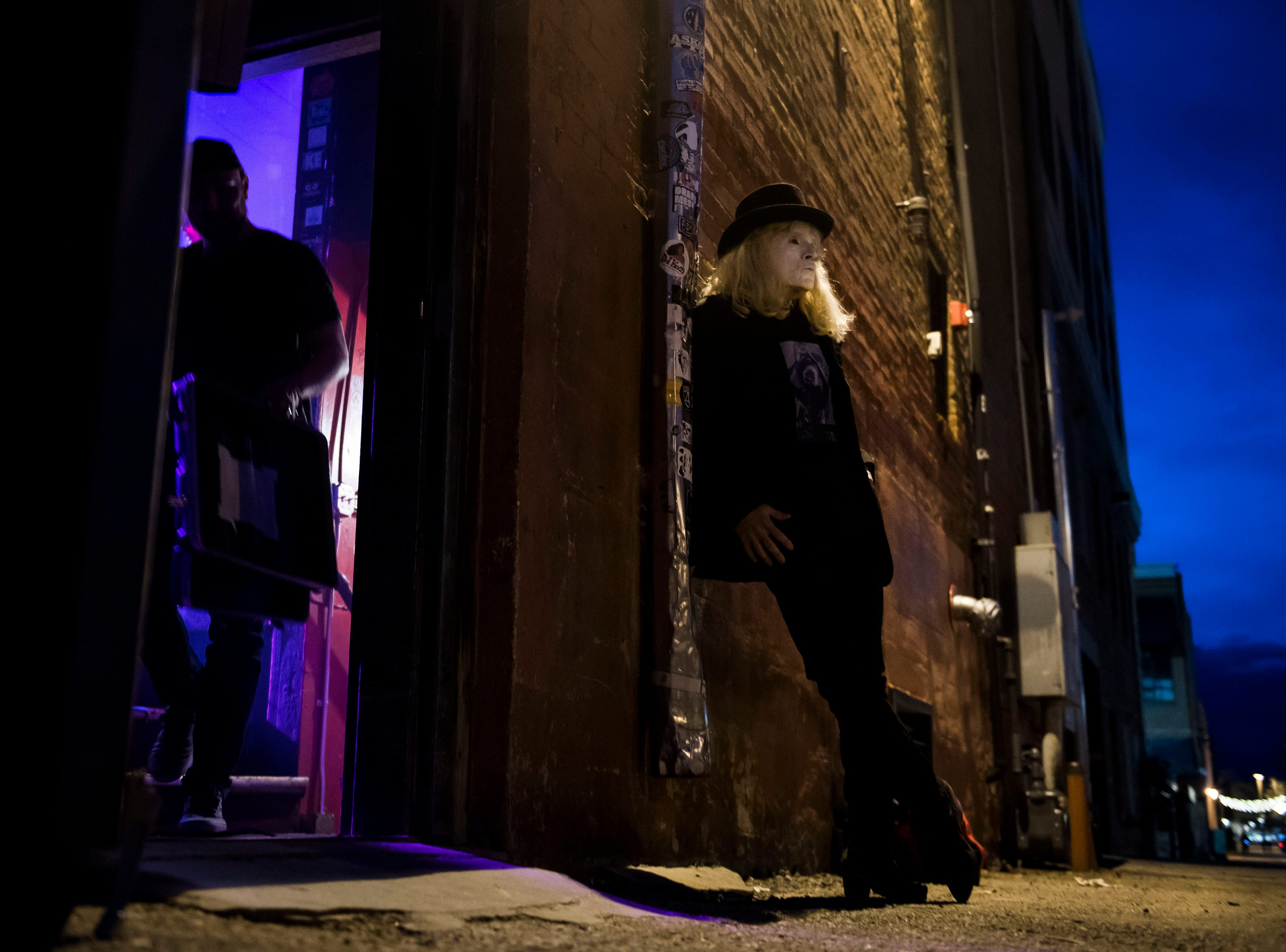 The Velveteers' Ozzie leans against the wall at the back alley entrance of The Aggie Theatre while waiting to take the stage during the FoCoMX XI music festival on Friday, April 26, 2019, in Fort Collins, Colo.