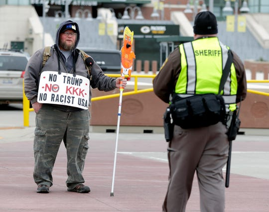 Bob Bergman of Oshkosh stands on Oneida Street to protest President Donald Trumps visit to Green Bay on April 27, 2019.