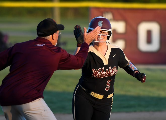 Webster County head coach Gregory Pirtle gives Webster County's Grace Scott (5) a high five as she runs past third base after hitting a three run home run in the sixth inning as the Webster County Lady Trojans play the Henderson County Lady Colonels at Henderson's North Field Friday, April 26, 2019.