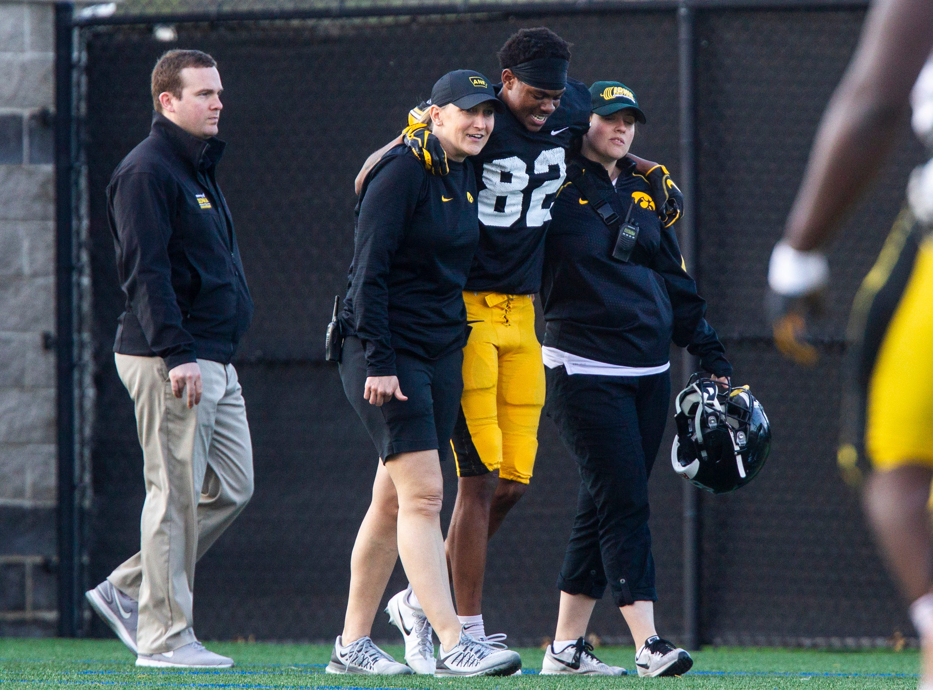 Iowa wide receiver Calvin Lockett (82) gets helped off the field by staff after getting tangled up on a contested ball during the final spring football practice, Friday, April 26, 2019, at the University of Iowa outdoor practice facility in Iowa City, Iowa.