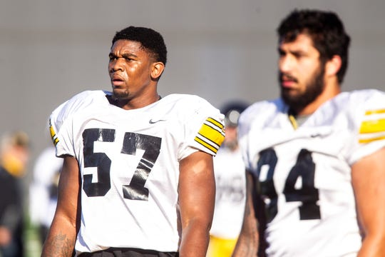 Iowa's junior defensive ends Chauncey Golston (57) and A.J. Epenesa rest between drills during Friday's final spring practice. Epenesa is seen as a potential first-round NFL Draft choice next April. Golston may earn his shot to go to the next level as well.