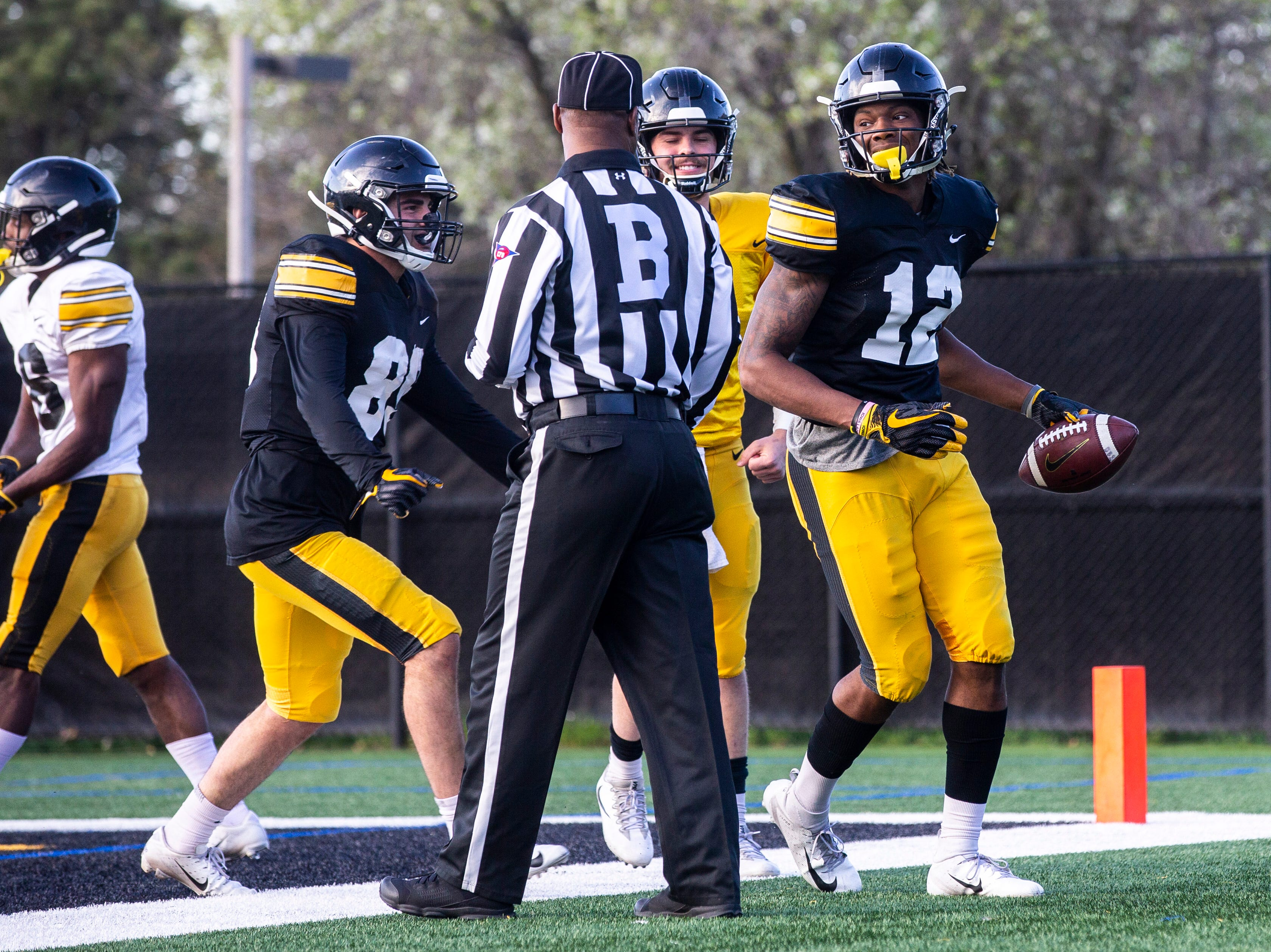 Iowa wide receiver Brandon Smith (12) gets embraced by teammates Nico Ragaini (89) and quarterback Peyton Mansell after catching a touchdown pass during the final spring football practice, Friday, April 26, 2019, at the University of Iowa outdoor practice facility in Iowa City, Iowa.