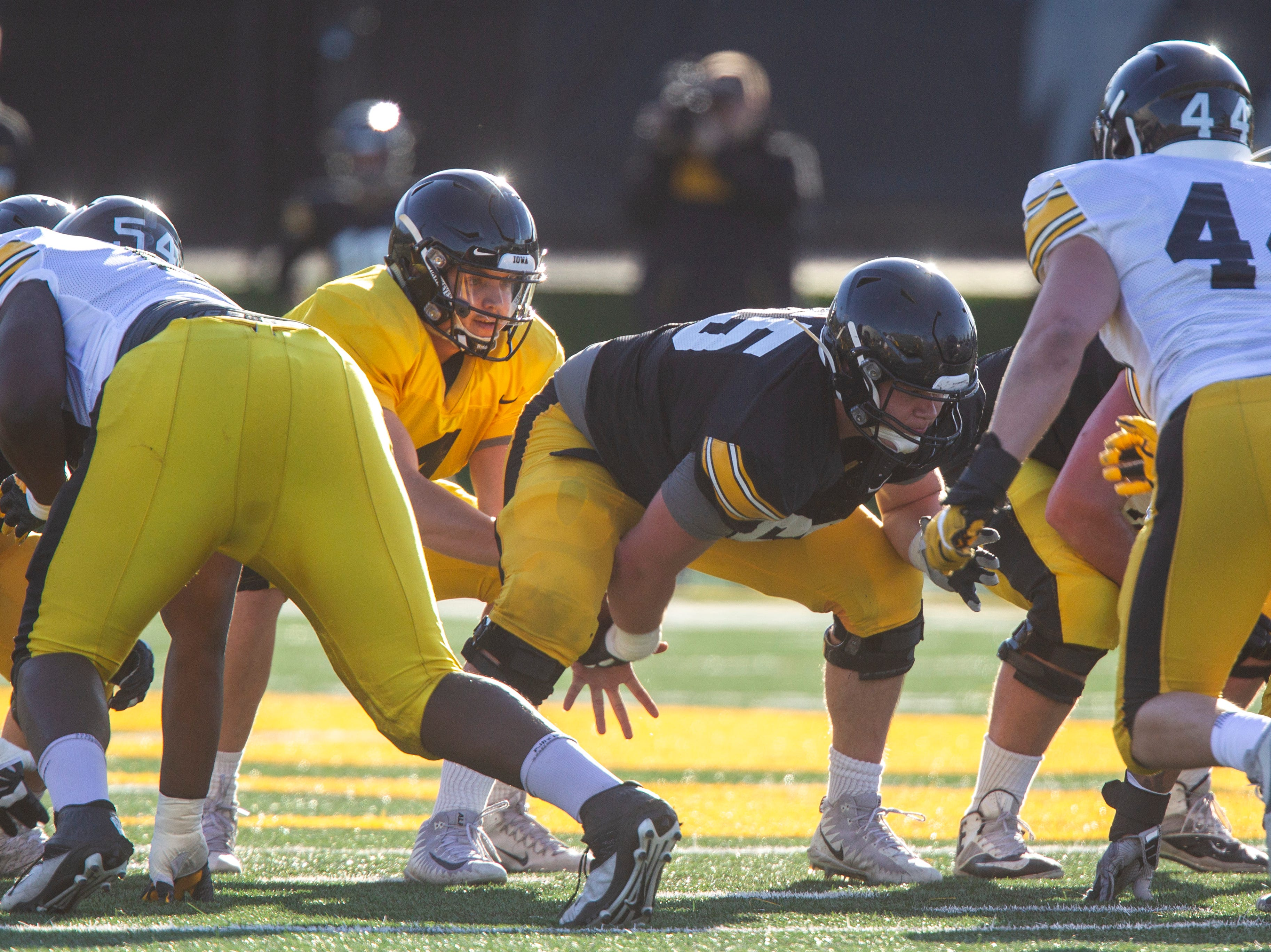 Iowa center Tyler Linderbaum (65) snaps the ball to quarterback Nate Stanley (4) during the final spring football practice, Friday, April 26, 2019, at the University of Iowa outdoor practice facility in Iowa City, Iowa.