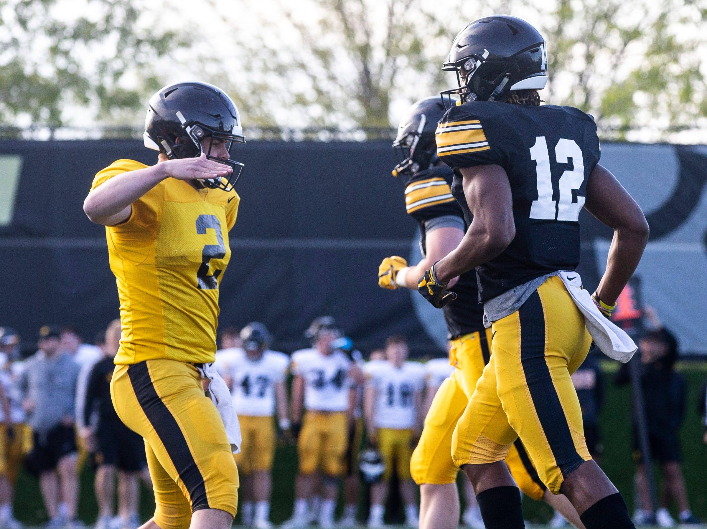 Iowa quarterback Peyton Mansell (2) high-fives teammate Brandon Smith (12) after his touchdown catch during the final spring football practice, Friday, April 26, 2019, at the University of Iowa outdoor practice facility in Iowa City, Iowa.