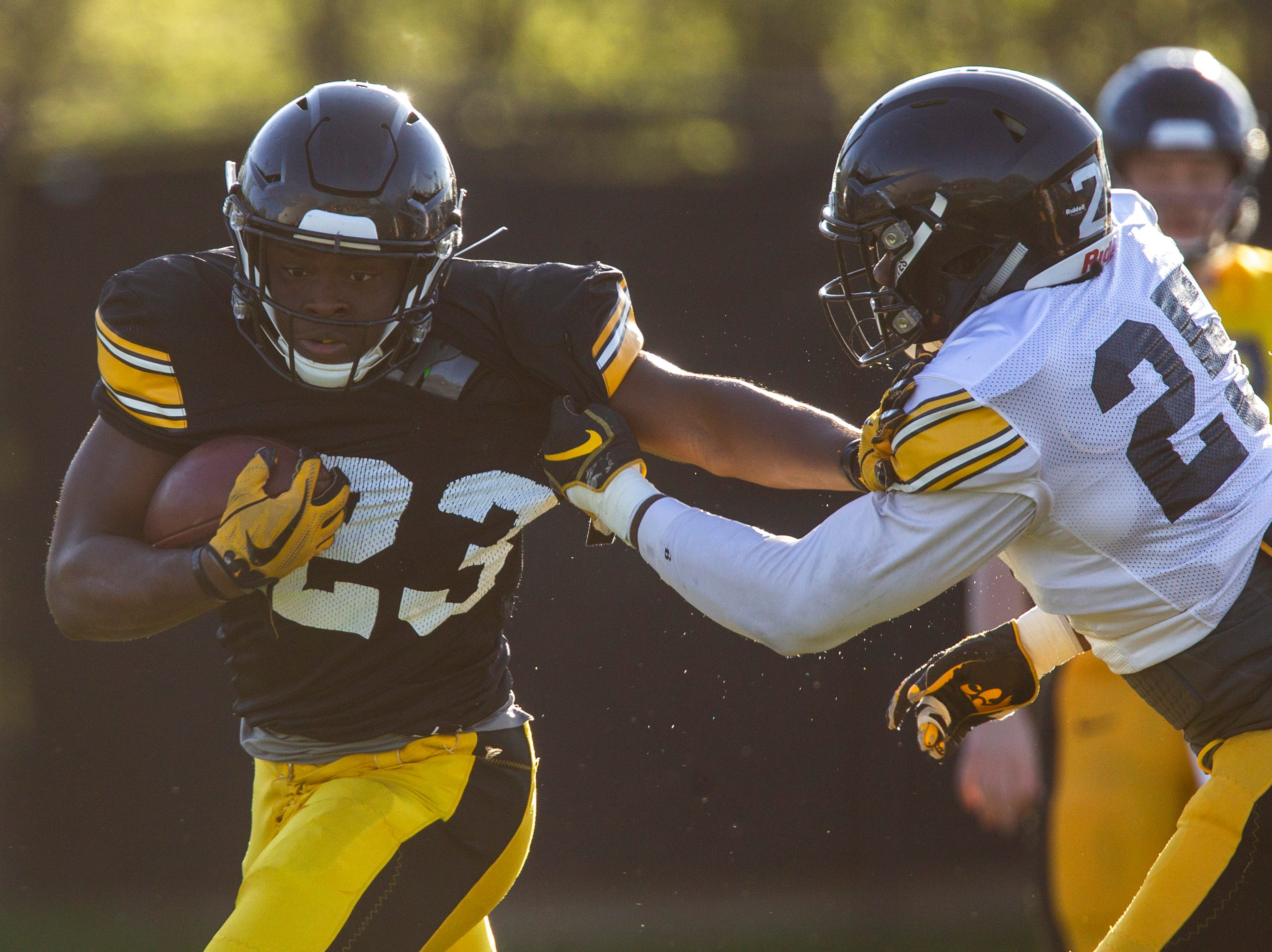 Iowa running back Shadrick Byrd (23) stiff arms linebacker Jayden McDonald (25) during the final spring football practice, Friday, April 26, 2019, at the University of Iowa outdoor practice facility in Iowa City, Iowa.