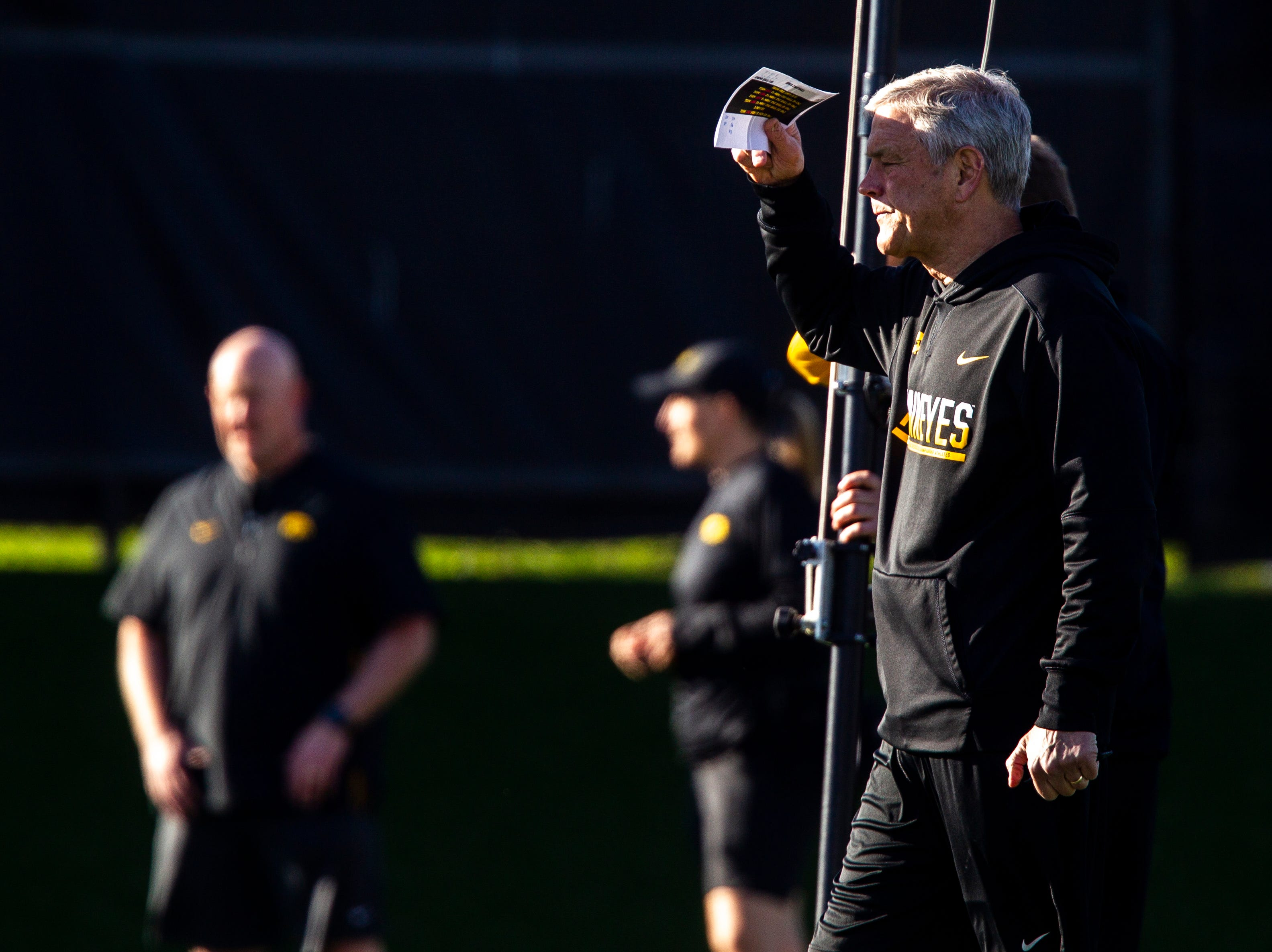 Iowa head coach Kirk Ferentz shields his eyes from the sun during the final spring football practice, Friday, April 26, 2019, at the University of Iowa outdoor practice facility in Iowa City, Iowa.