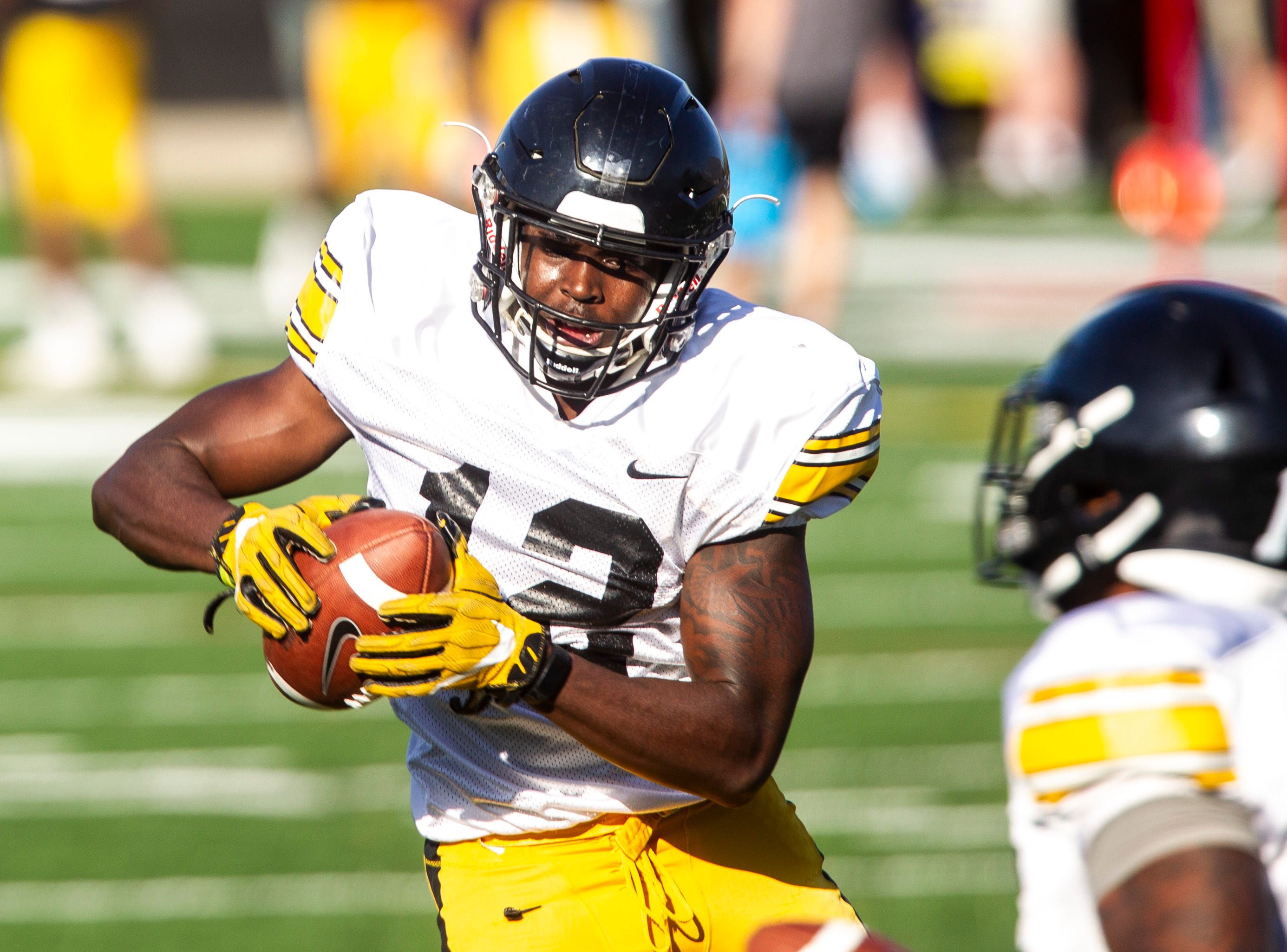 Iowa defensive back D.J. Johnson (12) catches a pass while running a drill during the final spring football practice, Friday, April 26, 2019, at the University of Iowa outdoor practice facility in Iowa City, Iowa.