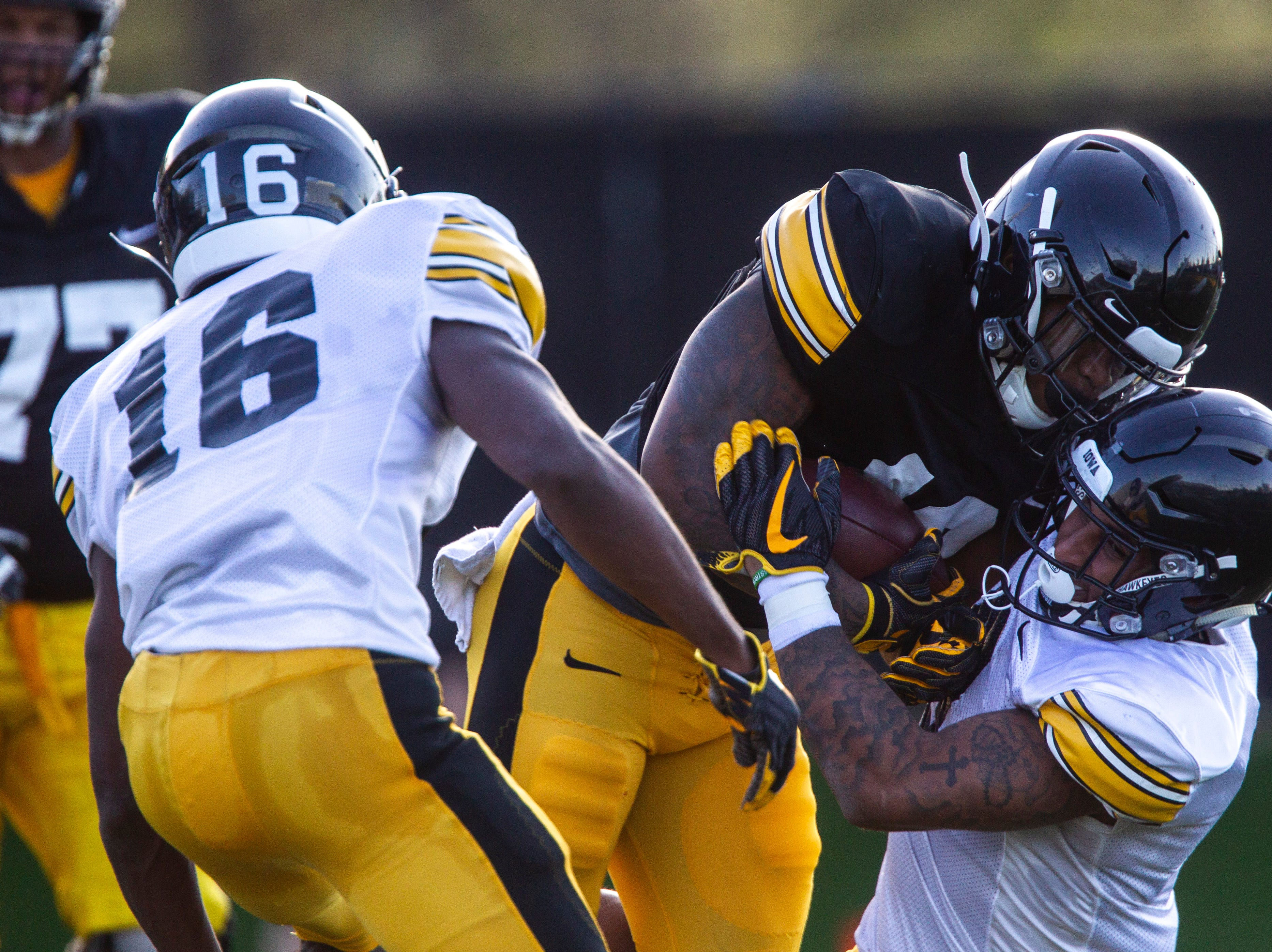 Iowa running back Mekhi Sargent (10) gets tackled by defensive back Geno Stone (9) during the final spring football practice, Friday, April 26, 2019, at the University of Iowa outdoor practice facility in Iowa City, Iowa.