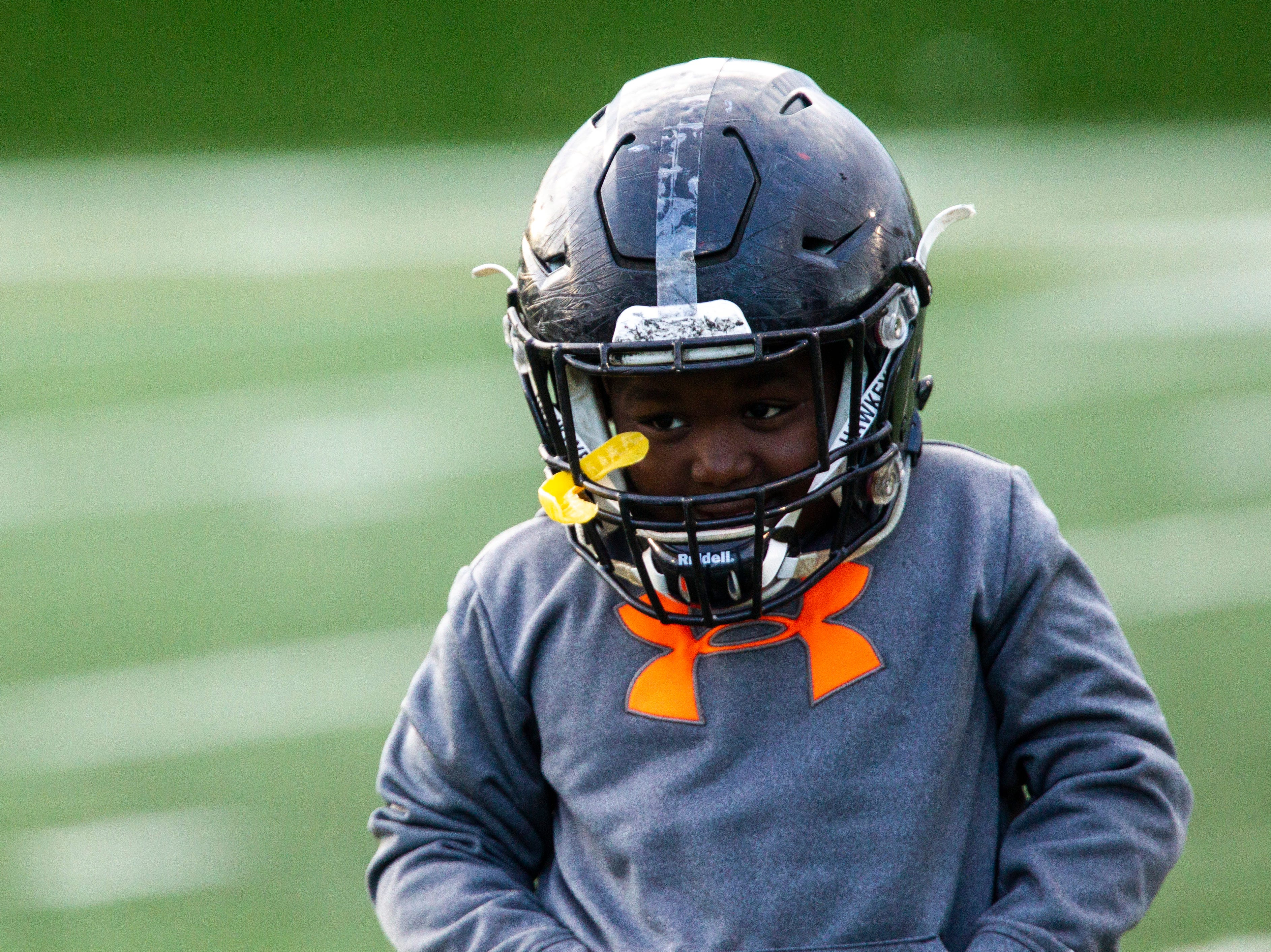 Iowa defensive tackle Daviyon Nixon's brother, Kevyn K.G. Nixon, 7, wears his helmet after the final spring football practice, Friday, April 26, 2019, at the University of Iowa outdoor practice facility in Iowa City, Iowa.