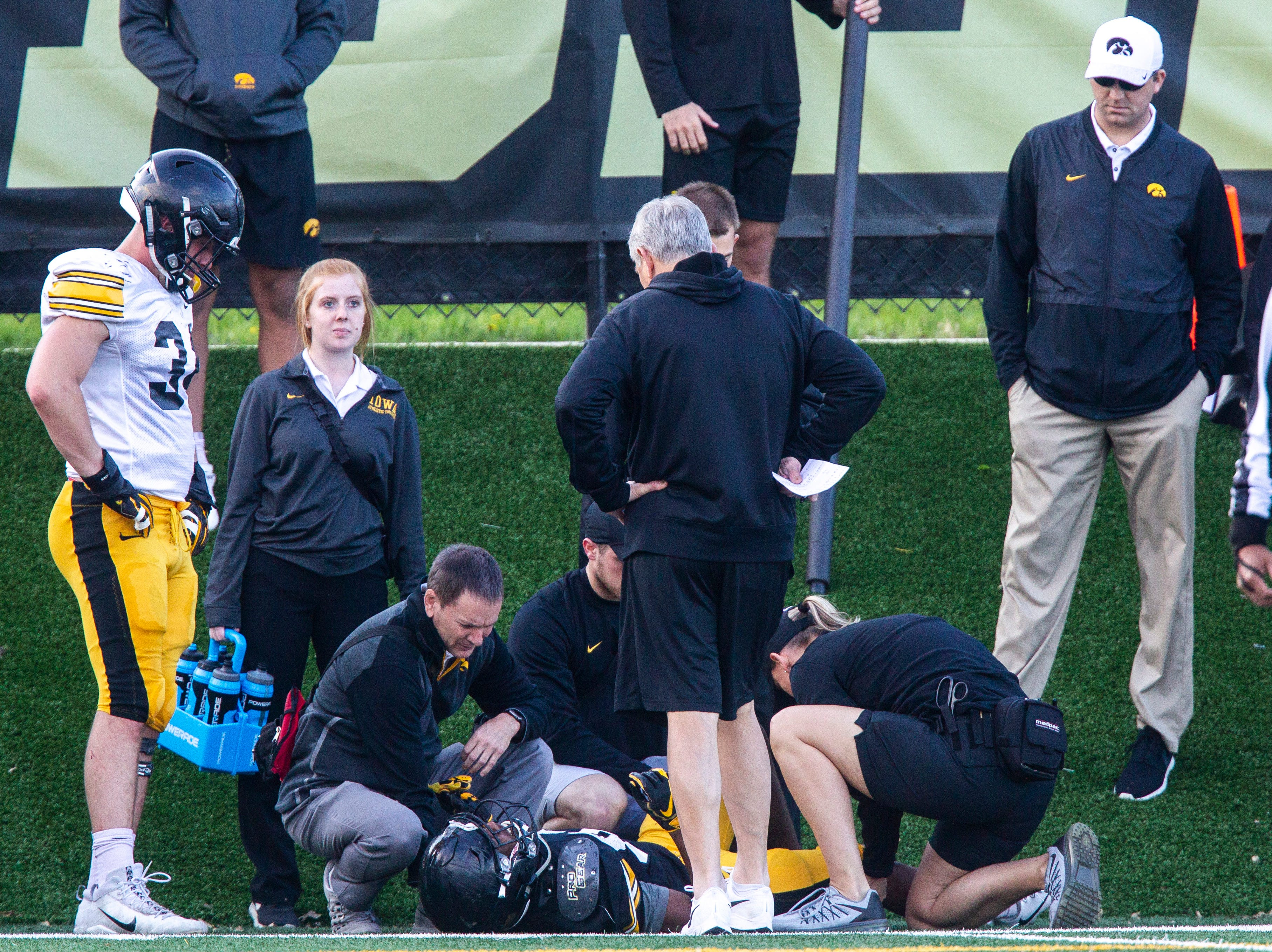 Iowa linebacker Kristian Welch, left, stands with head coach Kirk Ferentz next to wide receiver Calvin Lockett (82) as he gets helped by staff after getting tangled up on a contested ball during the final spring football practice, Friday, April 26, 2019, at the University of Iowa outdoor practice facility in Iowa City, Iowa.