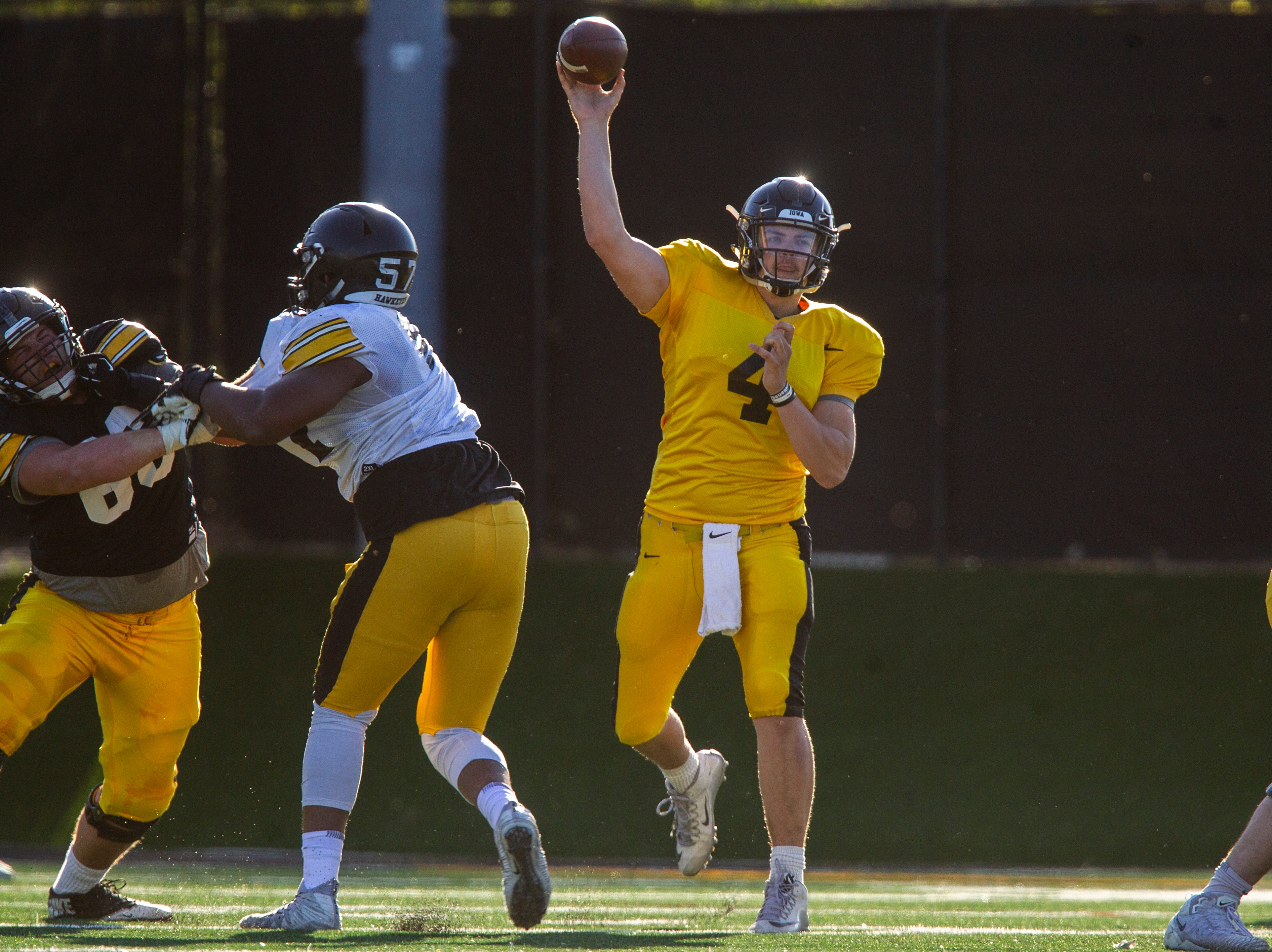 Iowa quarterback Nate Stanley (4) throws a pass as Levi Paulsen (66) blocks during the final spring football practice, Friday, April 26, 2019, at the University of Iowa outdoor practice facility in Iowa City, Iowa.