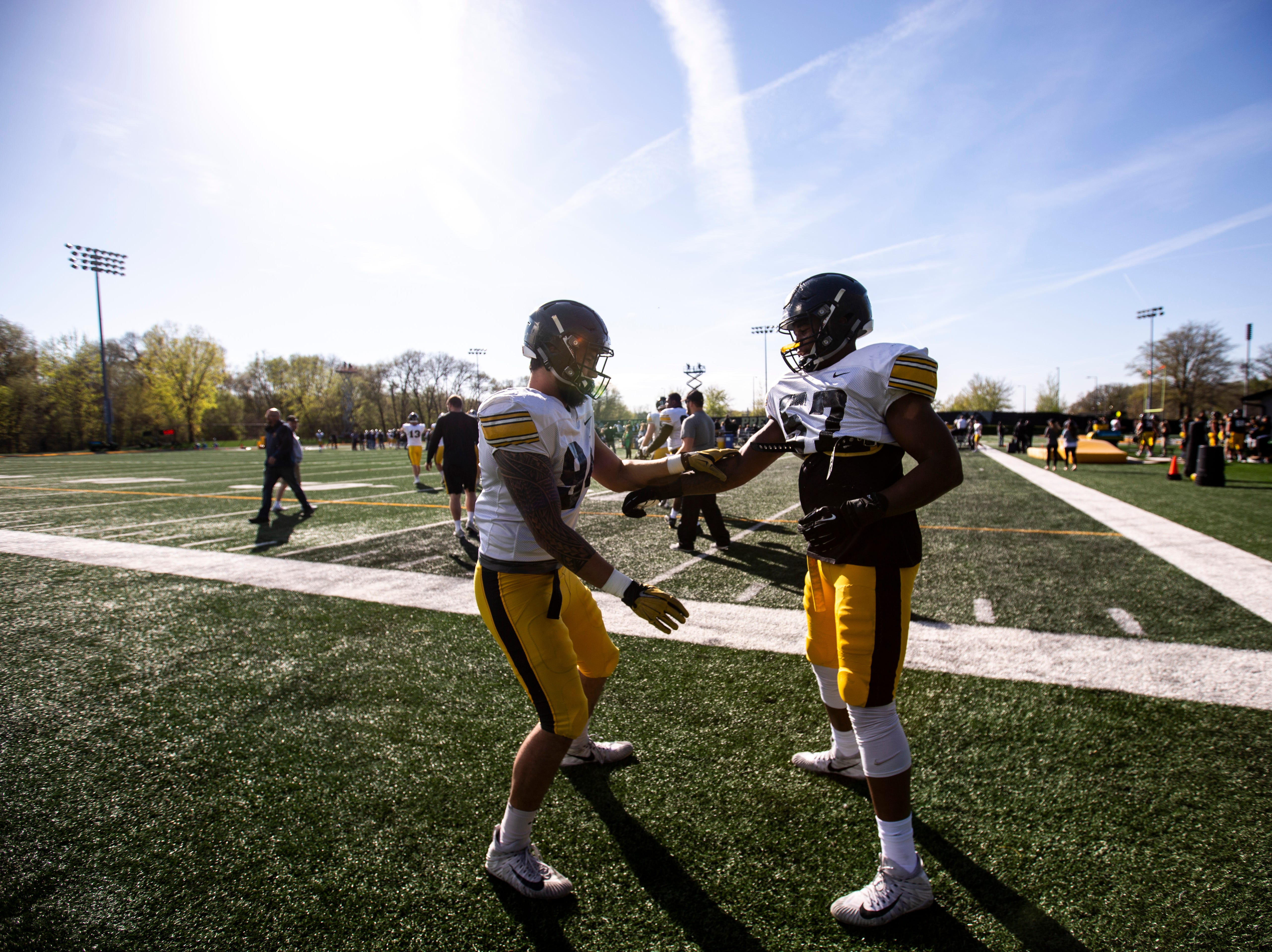 Iowa defensive end A.J. Epenesa (94) and defensive lineman Chauncey Golston (57) joke around during the final spring football practice, Friday, April 26, 2019, at the University of Iowa outdoor practice facility in Iowa City, Iowa.