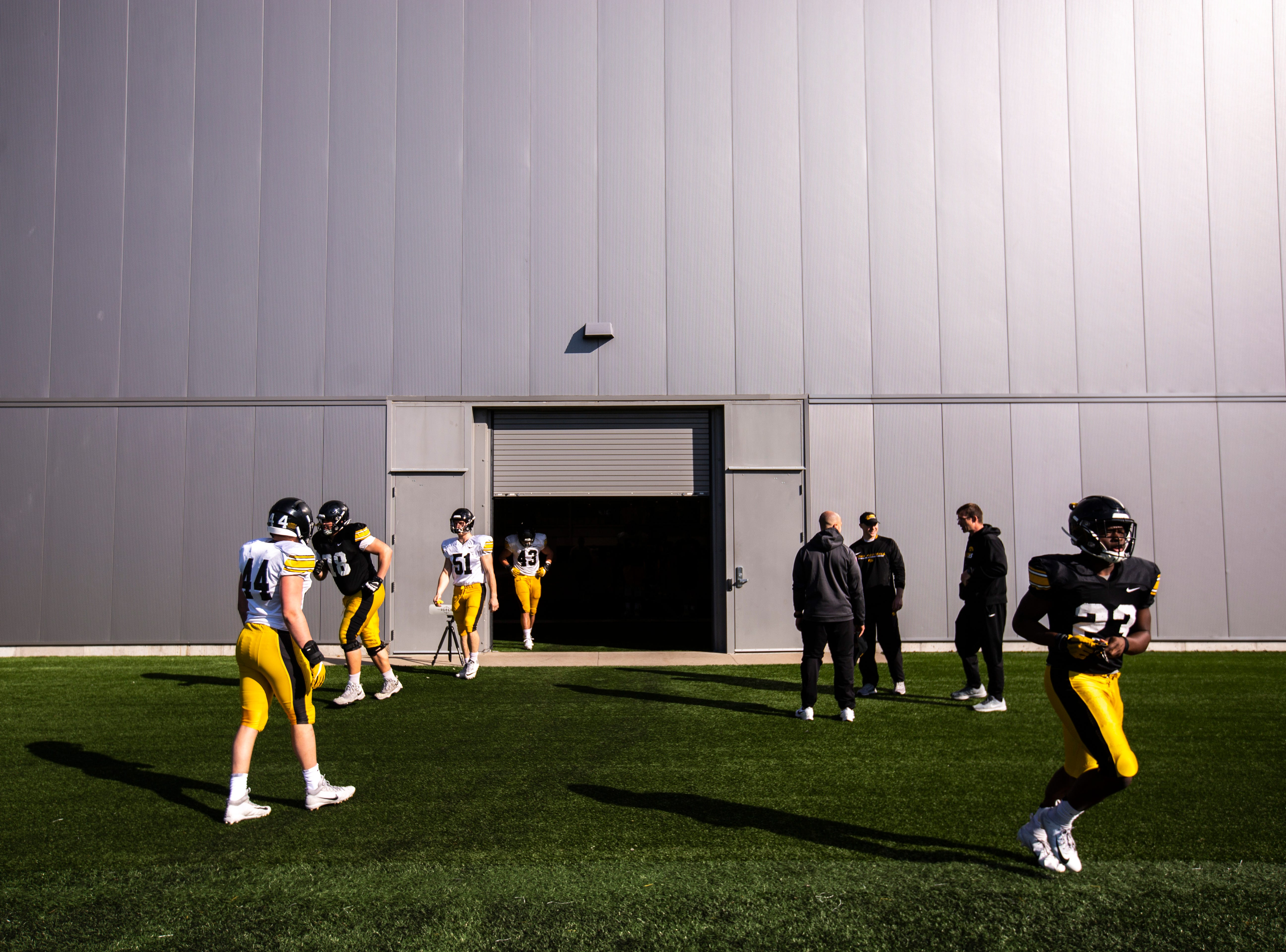 Iowa Hawkeyes players run out of the indoor practice facility before the final spring football practice, Friday, April 26, 2019, at the University of Iowa outdoor practice facility in Iowa City, Iowa.