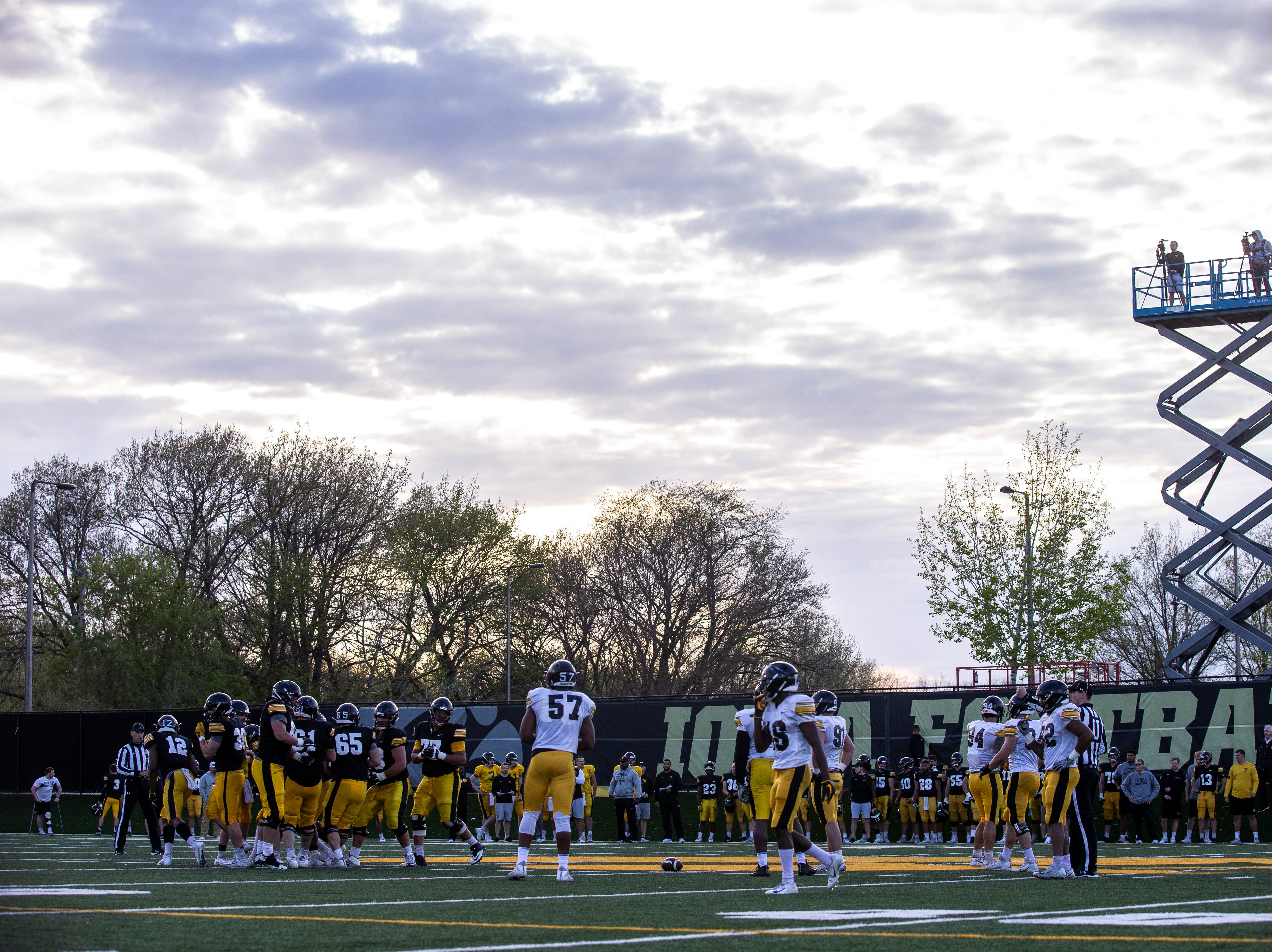 Iowa Hawkeyes line up as the sun beings to set during the final spring football practice, Friday, April 26, 2019, at the University of Iowa outdoor practice facility in Iowa City, Iowa.