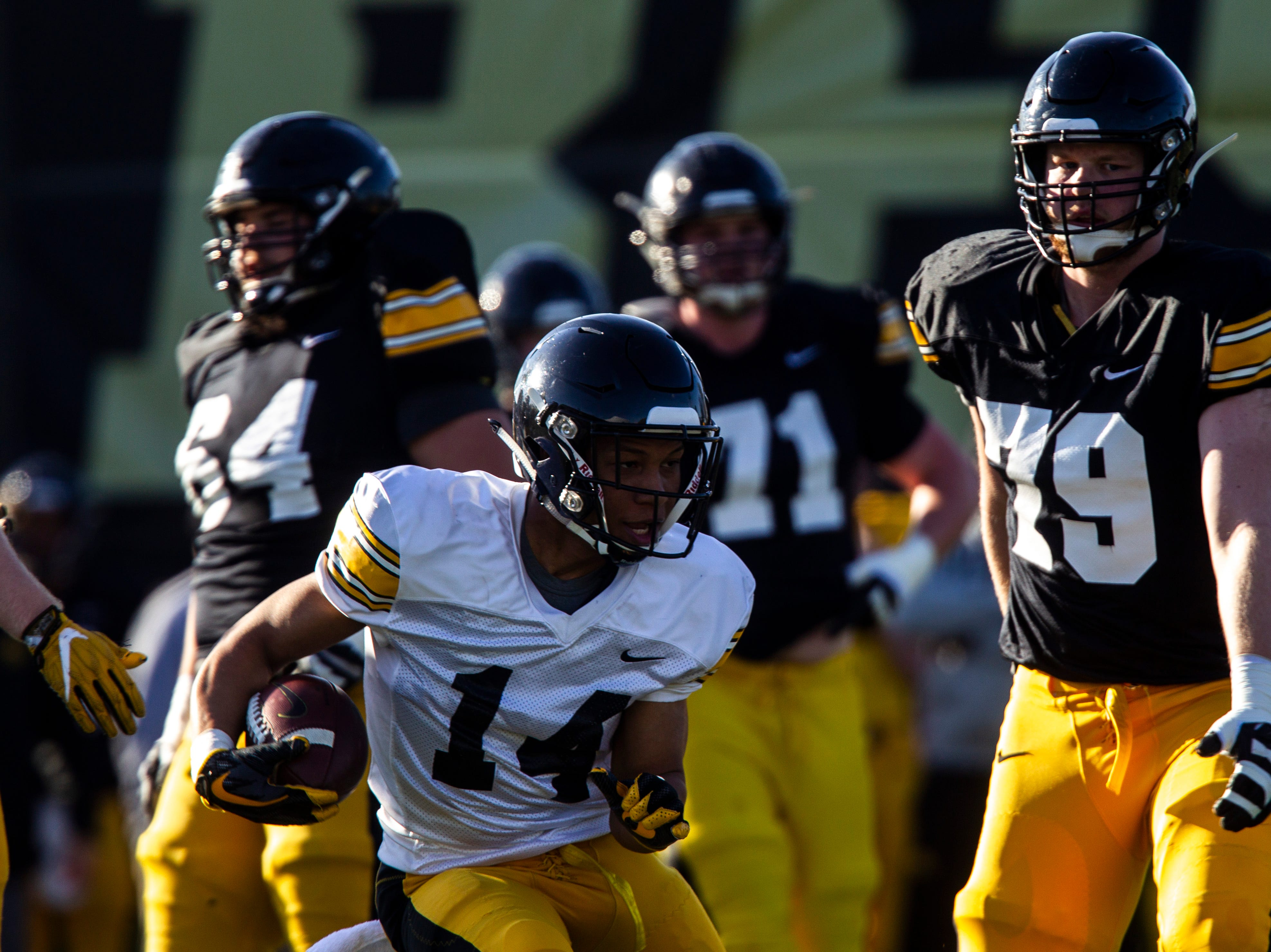 Iowa defensive back Daraun McKinney (14) returns an intercepted pass during the final spring football practice, Friday, April 26, 2019, at the University of Iowa outdoor practice facility in Iowa City, Iowa.
