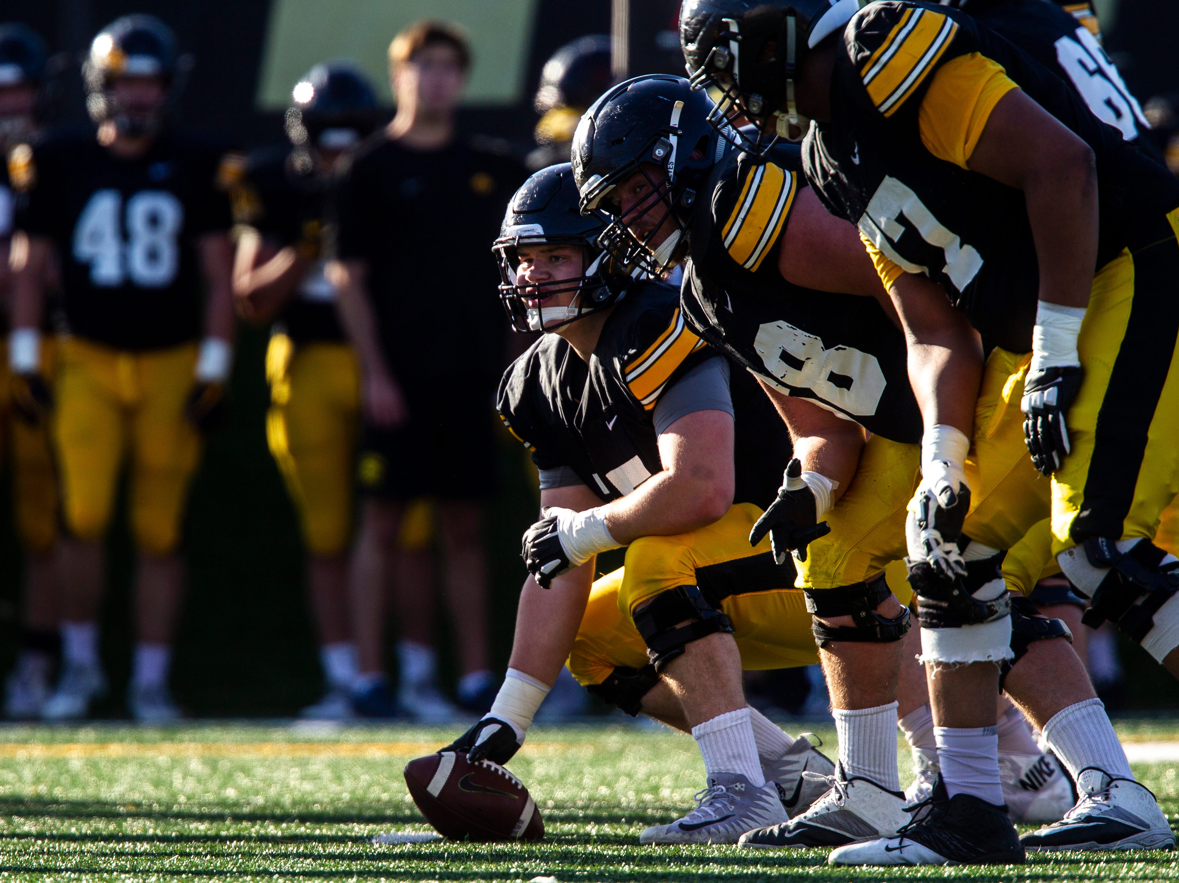 Iowa center Tyler Linderbaum (65) gets ready to snap the ball as offensive linemen Landan Paulsen and Alaric Jackson get set during the final spring football practice, Friday, April 26, 2019, at the University of Iowa outdoor practice facility in Iowa City, Iowa.