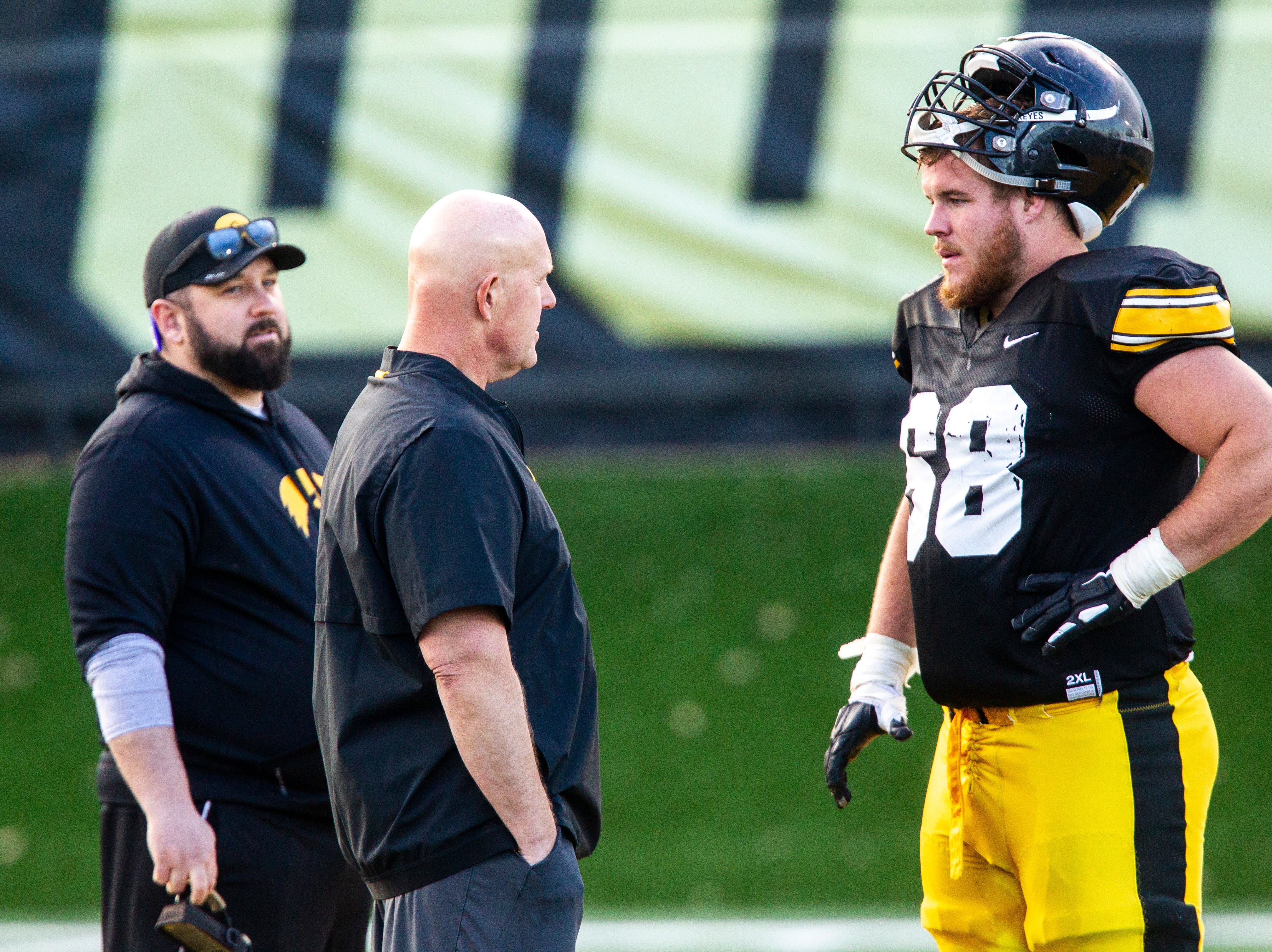 Iowa strength and conditioning coach Chris Doyle, second from left, talks with offensive lineman Landan Paulsen (68) after the final spring football practice, Friday, April 26, 2019, at the University of Iowa outdoor practice facility in Iowa City, Iowa.