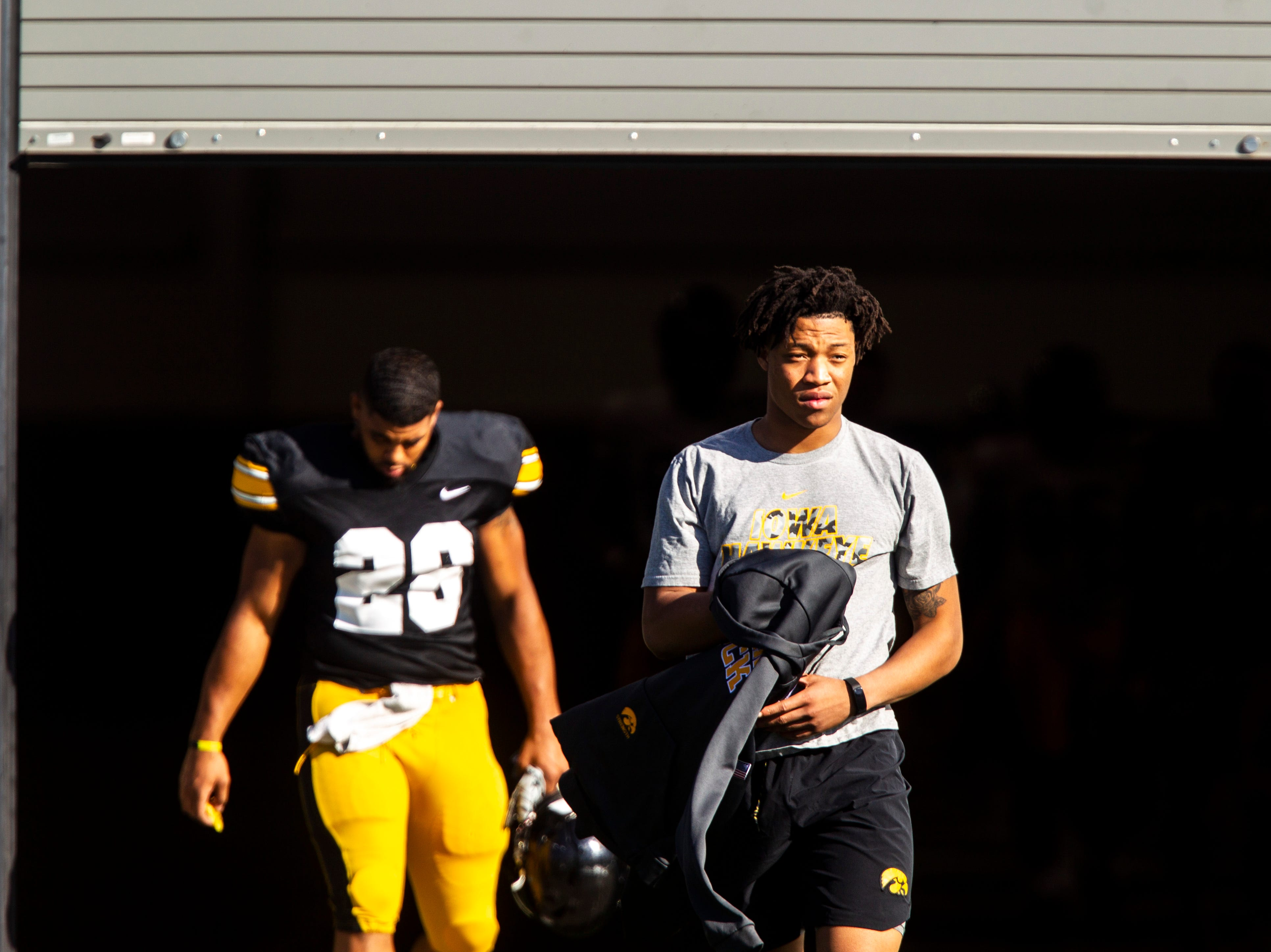 Iowa linebacker Jestin Jacobs, right, walks out to the field during the final spring football practice, Friday, April 26, 2019, at the University of Iowa outdoor practice facility in Iowa City, Iowa.
