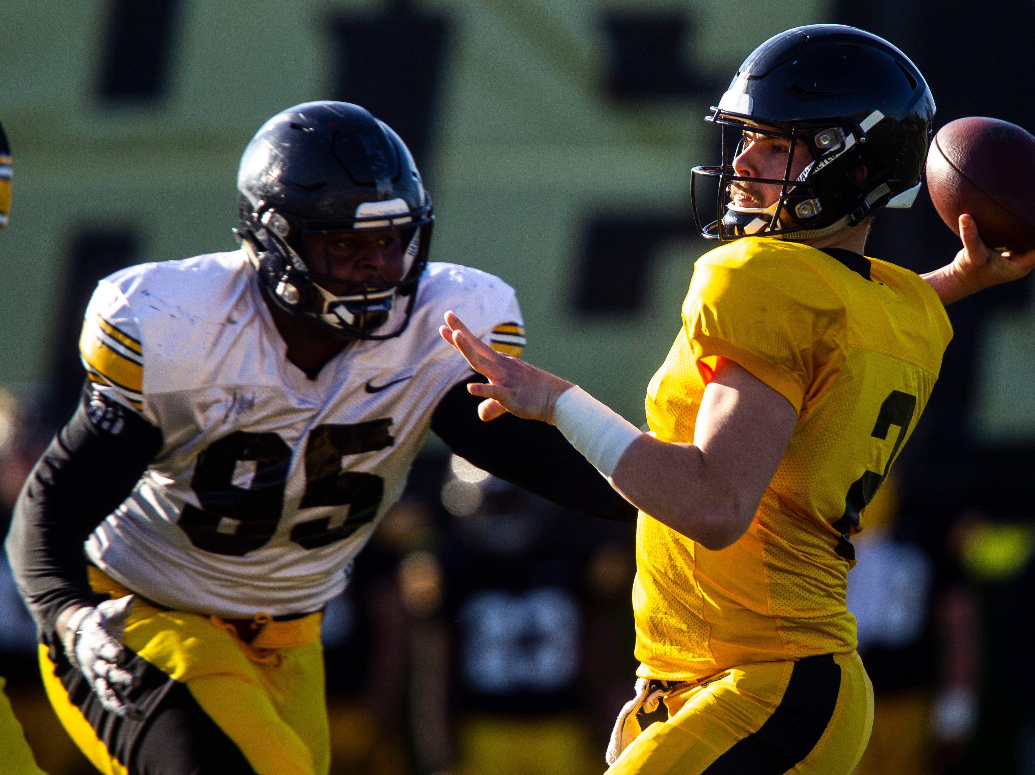Iowa quarterback Peyton Mansell (2) attempts to get a pass away while defensive lineman Cedrick Lattimore (95) brings pressure during the final spring football practice, Friday, April 26, 2019, at the University of Iowa outdoor practice facility in Iowa City, Iowa.