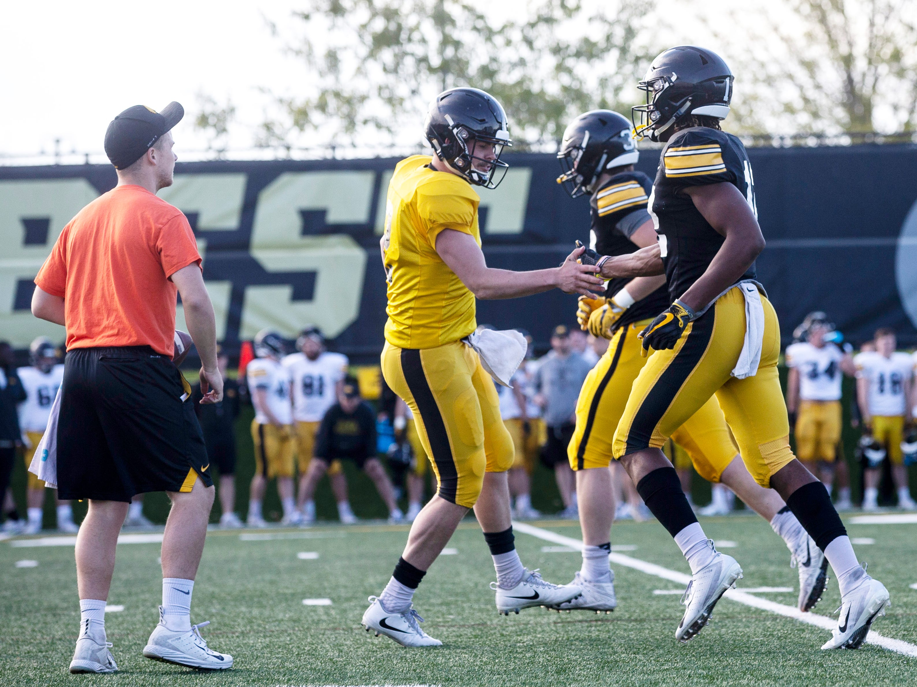 Iowa quarterback Peyton Mansell, second from left, high-fives teammate Brandon Smith (12) after he caught a touchdown pass during the final spring football practice, Friday, April 26, 2019, at the University of Iowa outdoor practice facility in Iowa City, Iowa.