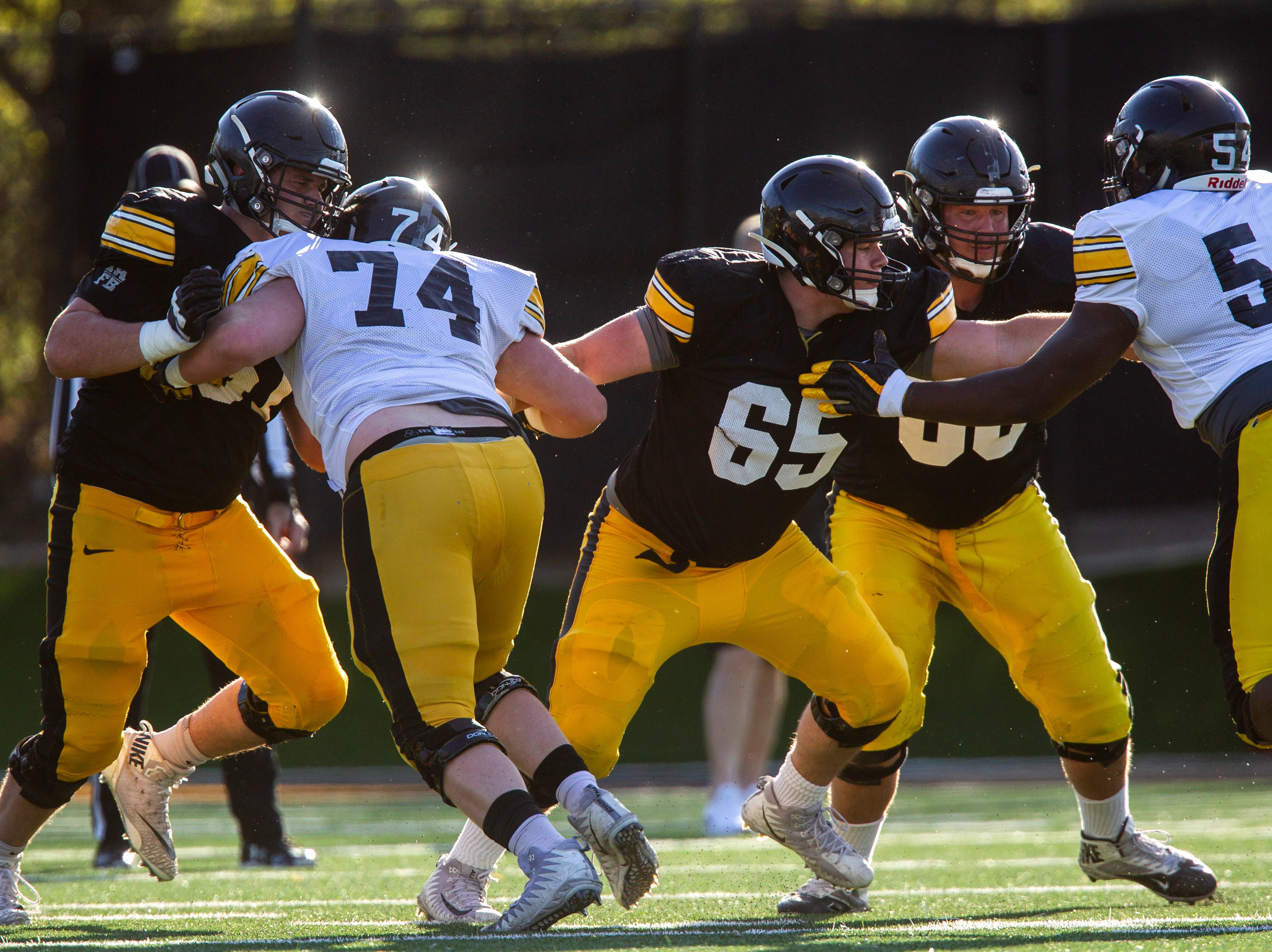 Iowa offensive lineman Cole Banwart, from left, Tyler Linderbaum (65) and Landan Paulsen, second from right, block during the final spring football practice, Friday, April 26, 2019, at the University of Iowa outdoor practice facility in Iowa City, Iowa.