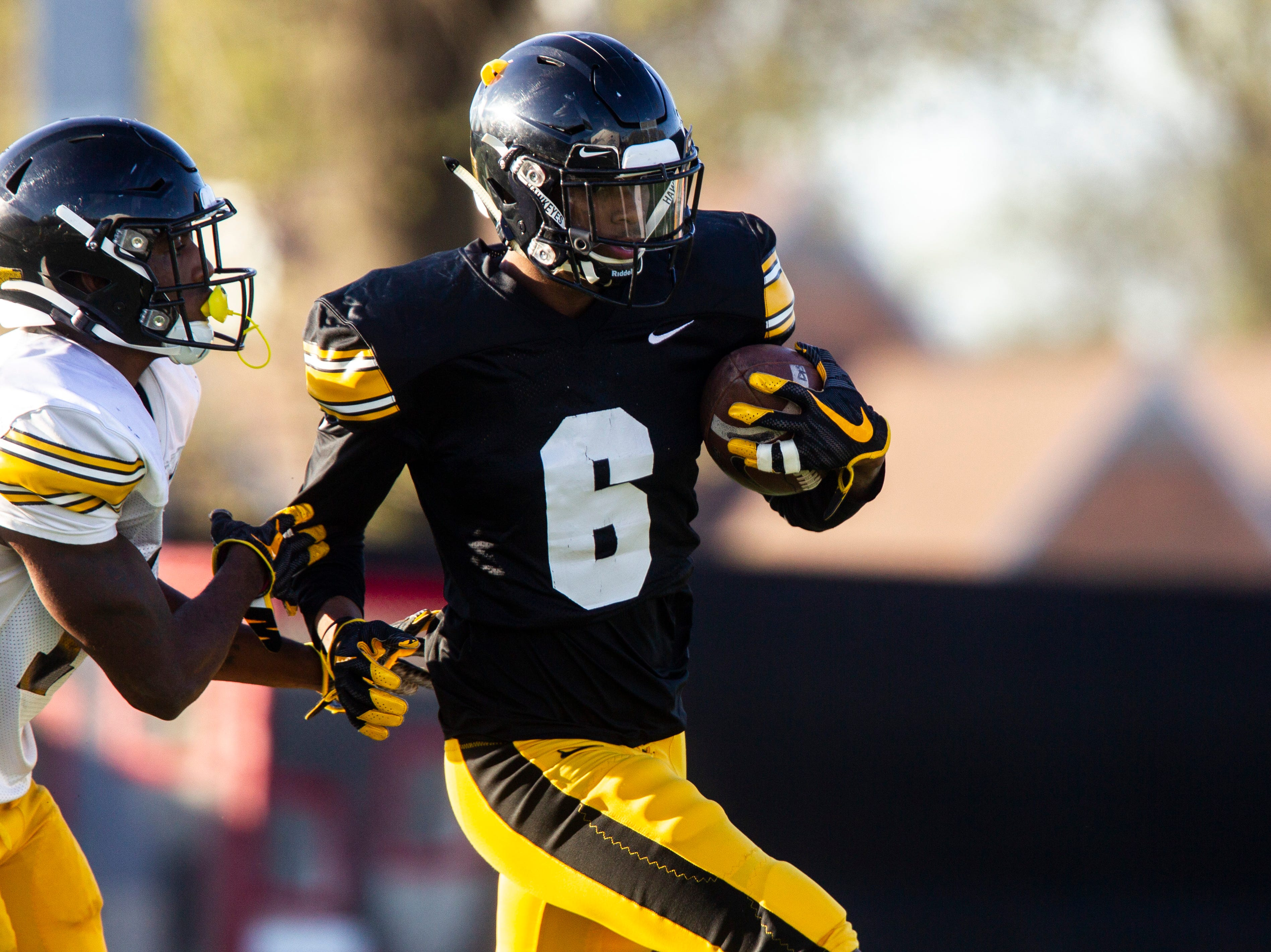 Iowa wide receiver Ihmir Smith-Marsette (6) returns a punt as defensive back Terry Roberts (16) closes in during the final spring football practice, Friday, April 26, 2019, at the University of Iowa outdoor practice facility in Iowa City, Iowa.