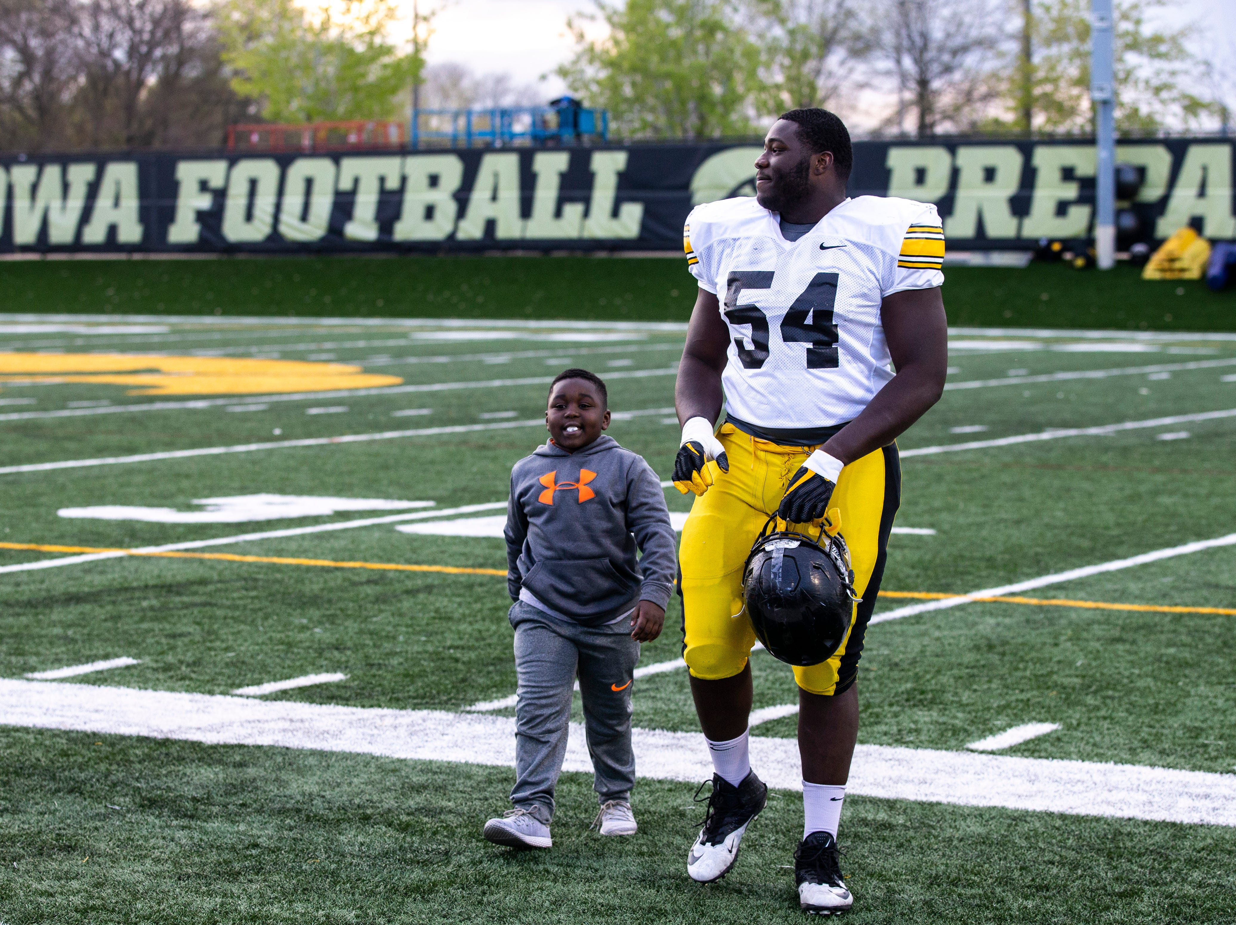 Iowa defensive tackle Daviyon Nixon (54) is greeted by his brother, Kevyn K.G. Nixon, 7, after the final spring football practice, Friday, April 26, 2019, at the University of Iowa outdoor practice facility in Iowa City, Iowa.