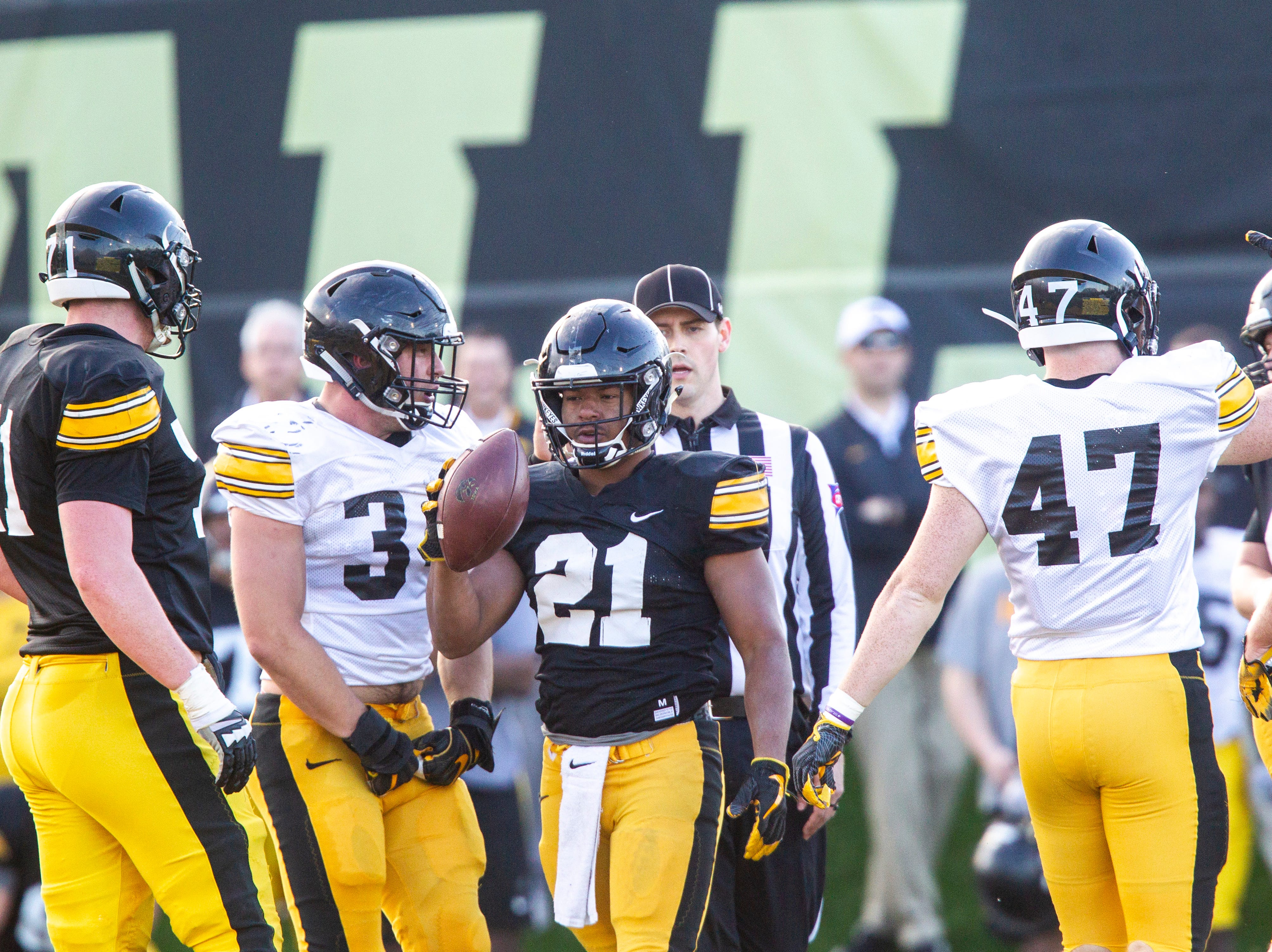 Iowa running back Ivory Kelly-Martin (21) walks back to the huddle as linebacker Kristian Welch (34) reacts to a stop during the final spring football practice, Friday, April 26, 2019, at the University of Iowa outdoor practice facility in Iowa City, Iowa.