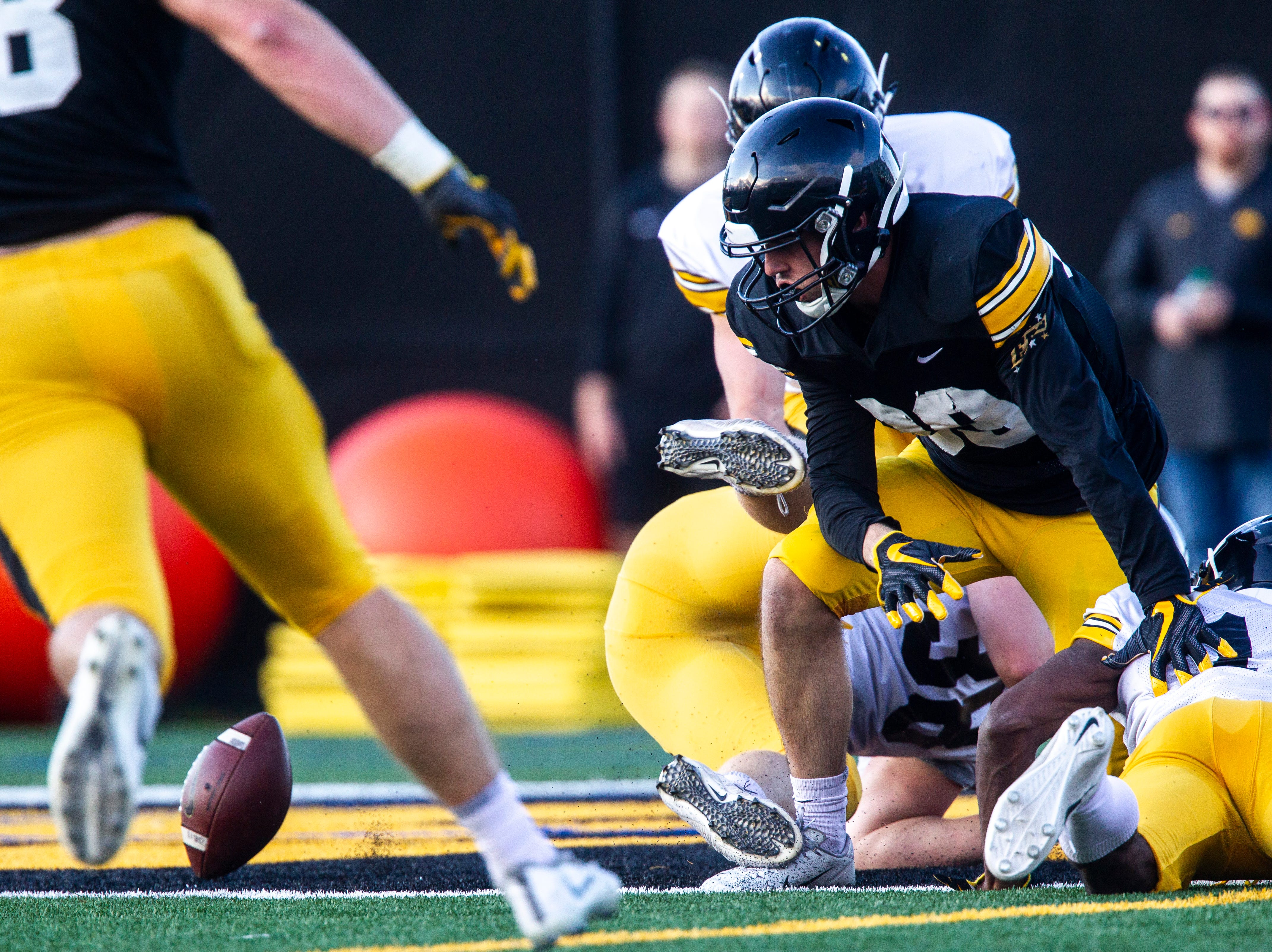 Iowa wide receiver Nico Ragaini scrambles to recover a near-goal-line fumble forced by defensive back Terry Roberts (16) during the final spring football practice, Friday, April 26, 2019, at the University of Iowa outdoor practice facility in Iowa City, Iowa.