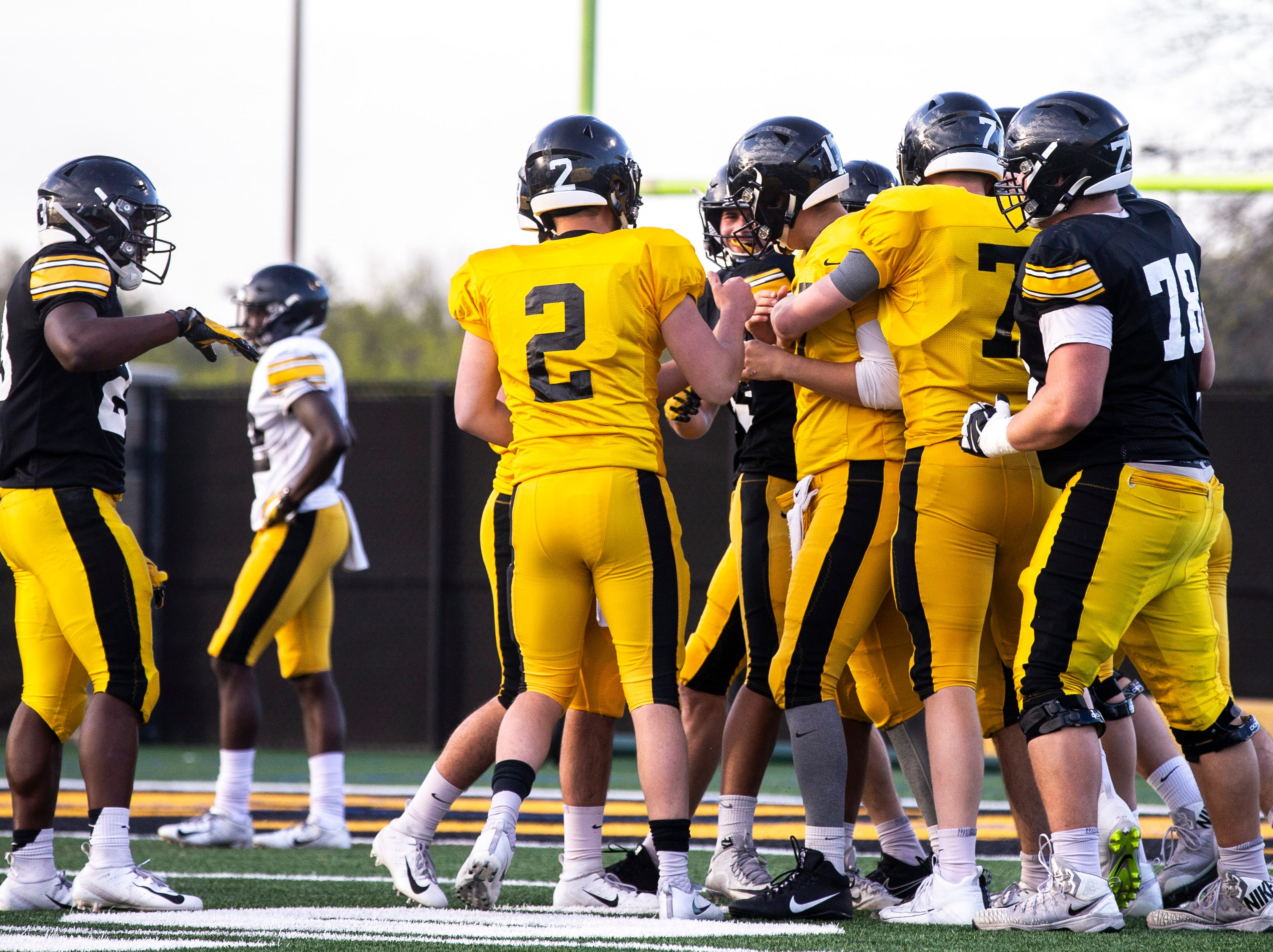 Iowa quarterback Ryan Schmidt (17) gets embraced by fellow quarterbacks Spencer Petras (7) and Peyton Mansell (2) after throwing a touchdown pass on the final play during the final spring football practice, Friday, April 26, 2019, at the University of Iowa outdoor practice facility in Iowa City, Iowa.