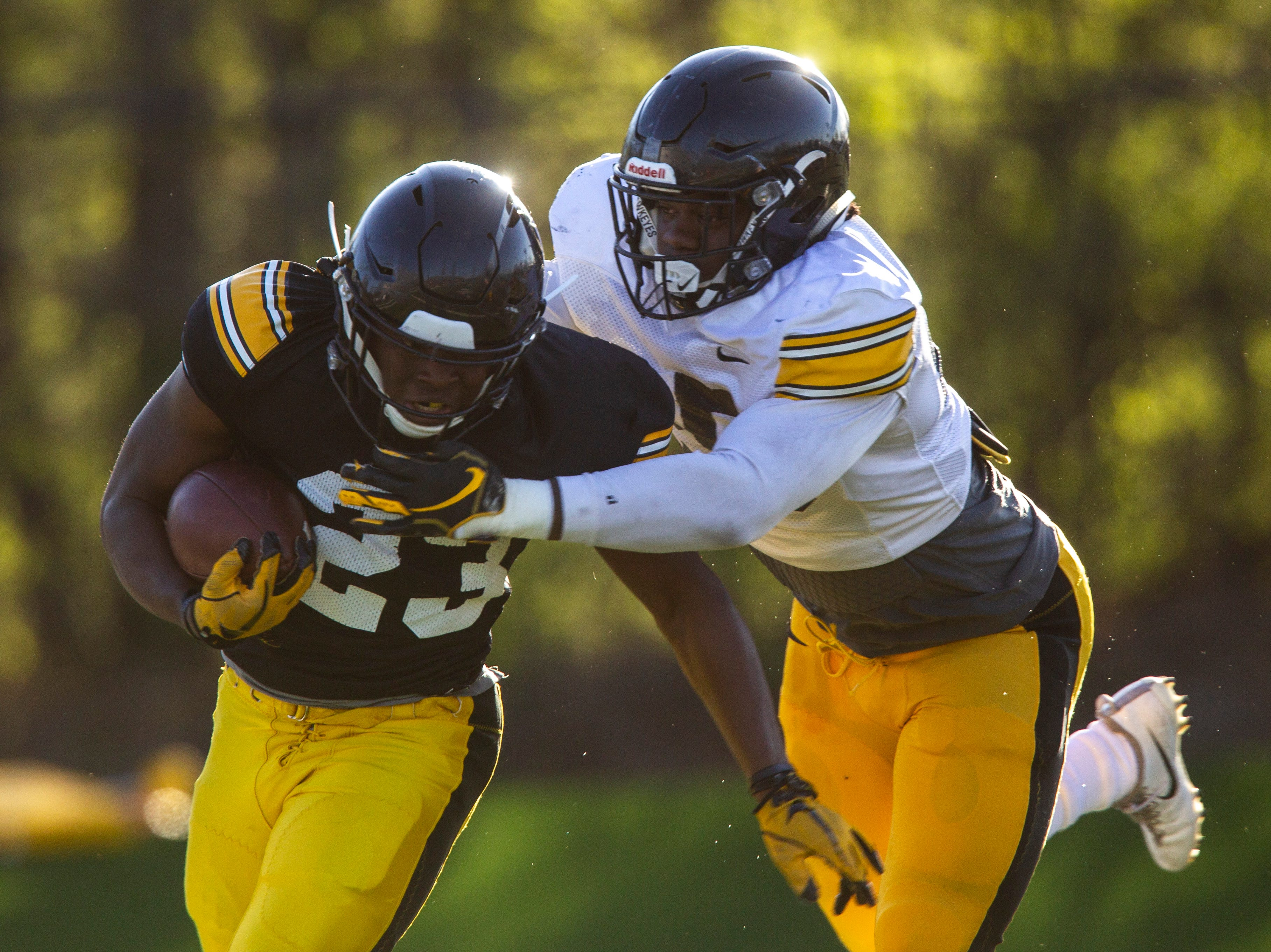 Iowa running back Shadrick Byrd (23) gets tackled by linebacker Jayden McDonald (25) during the final spring football practice, Friday, April 26, 2019, at the University of Iowa outdoor practice facility in Iowa City, Iowa.
