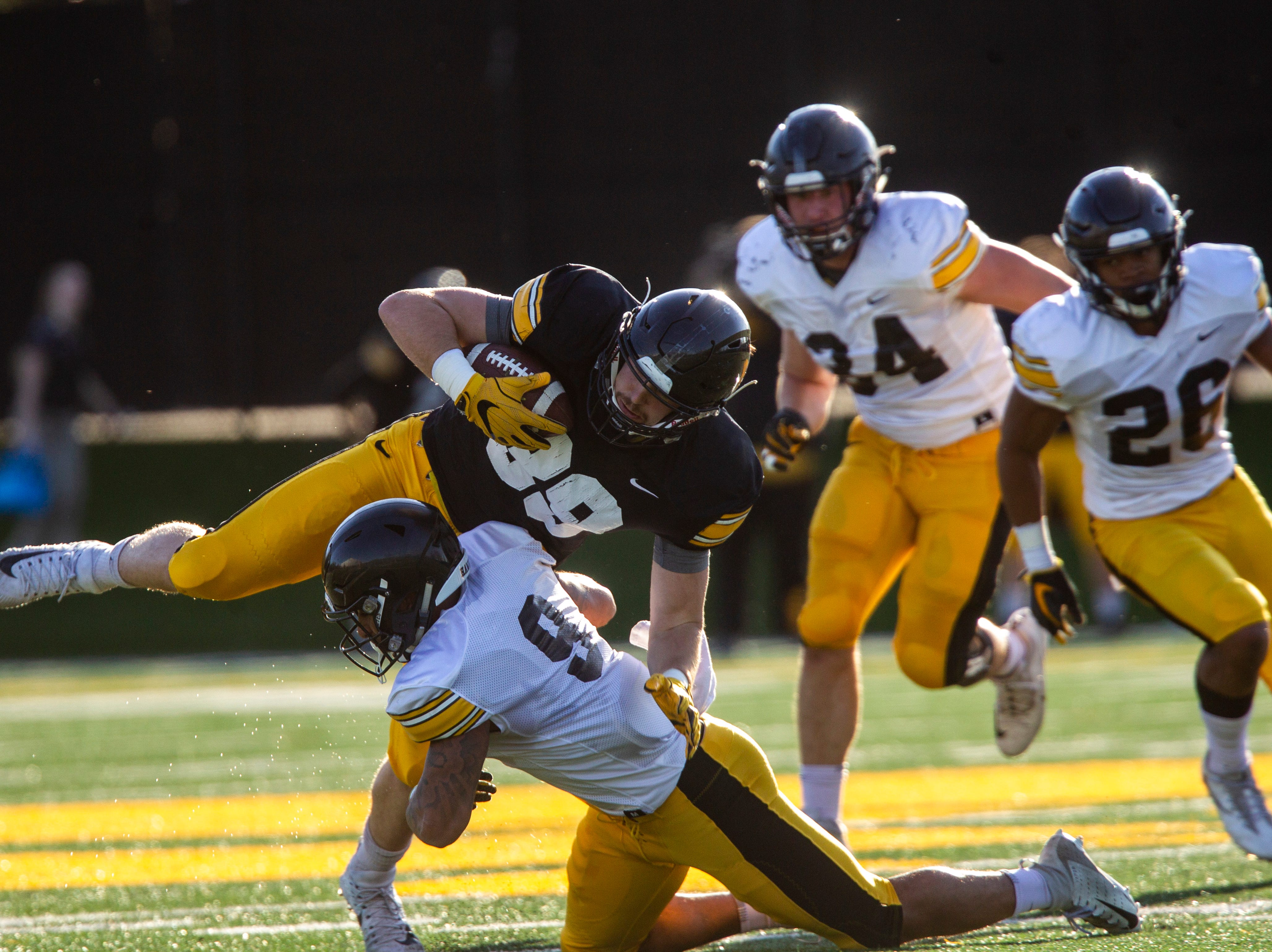 Iowa wide receiver Nico Ragaini (89) gets tackled by Geno Stone (9) during the final spring football practice, Friday, April 26, 2019, at the University of Iowa outdoor practice facility in Iowa City, Iowa.
