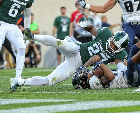 Aug 31, 2018; East Lansing, MI, USA; Utah State Aggies wide receiver Jordan Nathan (16) is tackled by Michigan State Spartans safety Khari Willis (27) during the first quarter of a game at Spartan Stadium. Mandatory Credit: Mike Carter-USA TODAY Sports
