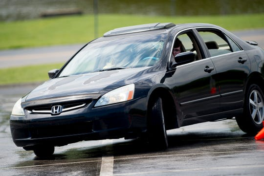 A driver comes around a turn during a Street Survival training course at Pellissippi State Community College in Hardin Valley in Knoxville, Tennessee on Saturday, April 27, 2019. Street Survival teaches teens how to drive in emergency situations using an obstacle course while driving their own vehicles.