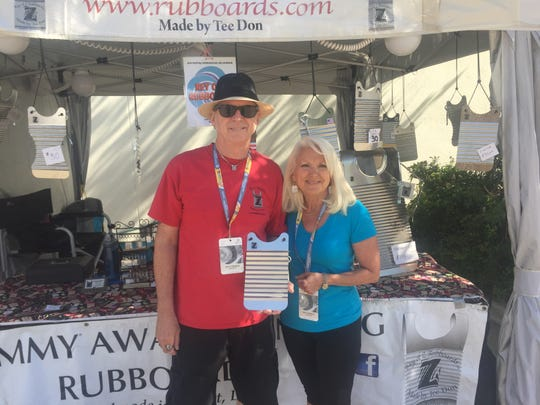 """""""Tee Don"""" Landry and his wife Kathy Landry sell rub-boards at Festival International"""
