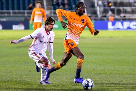 Lansing Ignite's Nathan Lewis, right, moves past Toronto FC II's Jordan Faria during the second half on Friday, April 26, 2019, at Cooley Law School Stadium in Lansing. Toronto beat Lansing 2-0.