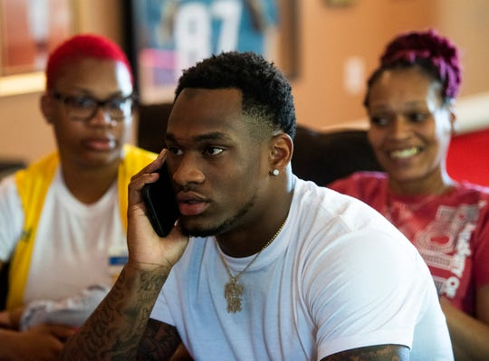 Mack Wilson talks on the phone with the Cleveland Browns as his sister Jakeesha Wyman and his mother Sandra Wilson look on during the third day of the NFL Draft on Saturday April 27, 2019 in Montgomery, Ala.