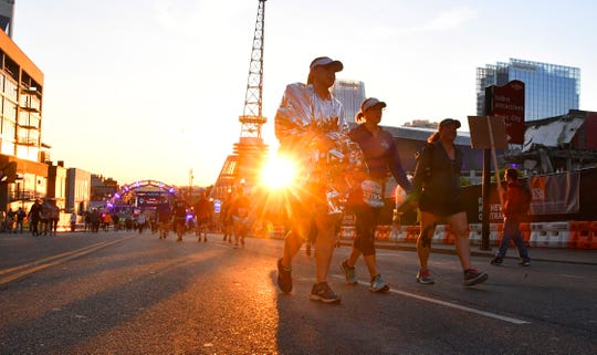 As the sun rises runners arrive on Broadway for the St. Jude Rock and Roll Marathon Saturday, April 27, 2019, in Nashville, Tenn.