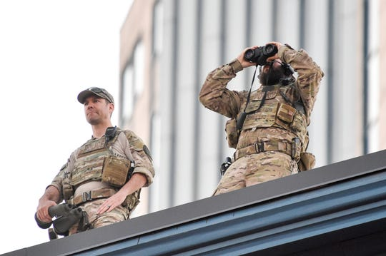 Police surveil from a rooftop on Lower Broadway during the NFL Draft Experience on Friday in Nashville. Metro police said they've made 10 draft-related arrests as of Saturday afternoon, mostly for public intoxication.