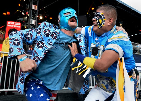 Tennessee Titans fan Daymond Foster, left, play wrestles with Los Angeles Chargers fan Guillermo Sandoval in front of the NFL Draft stage during the NFL Draft second round on Friday, April 26, 2019, in Nashville, Tenn.