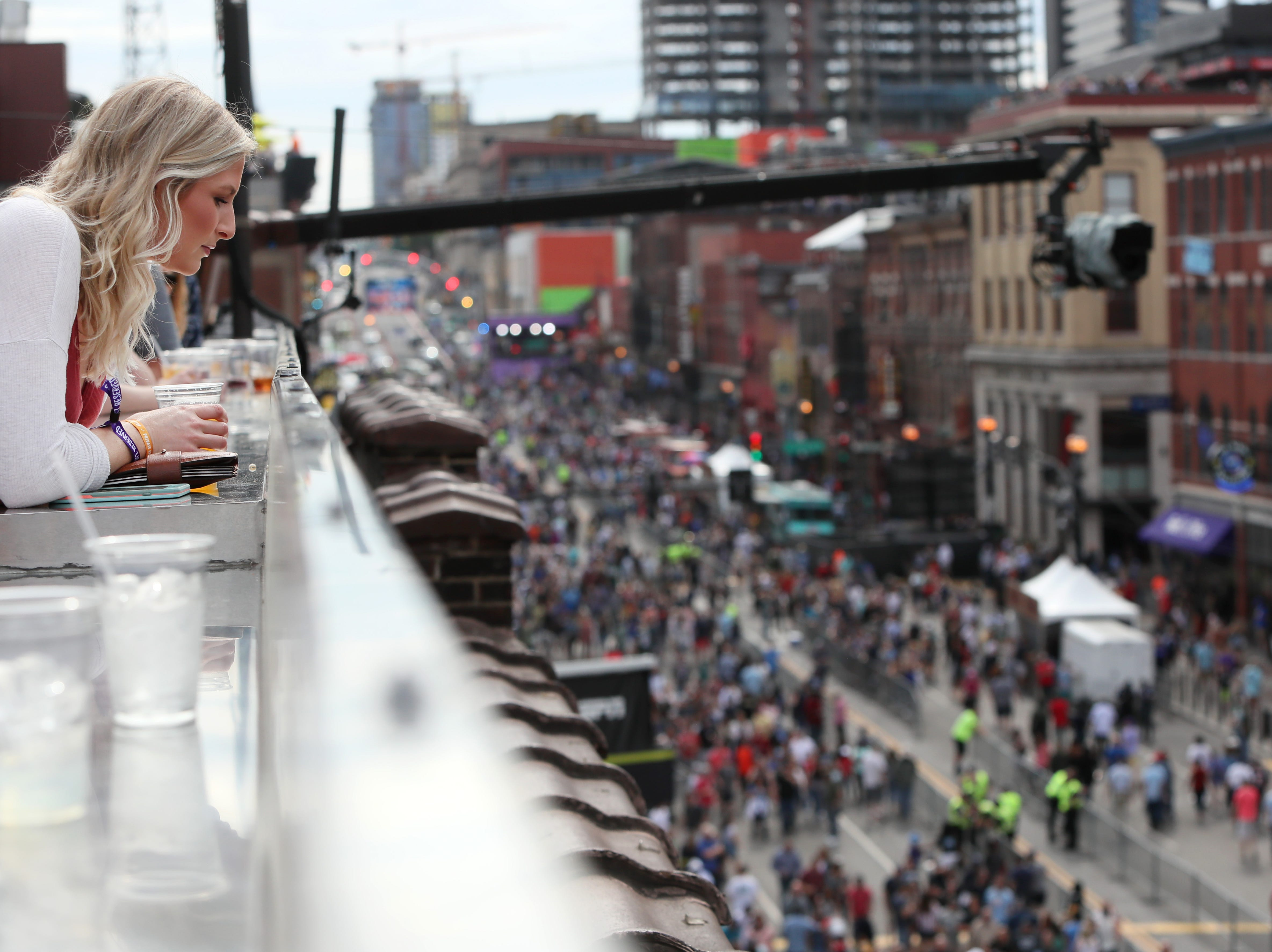 Morgan Musselwhite looks out over the crowd on Lower Broadway from the Rock Bottom Brewery rooftop deck during the NFL draft's third and final day in downtown Nashville on Saturday, April 27, 2019.