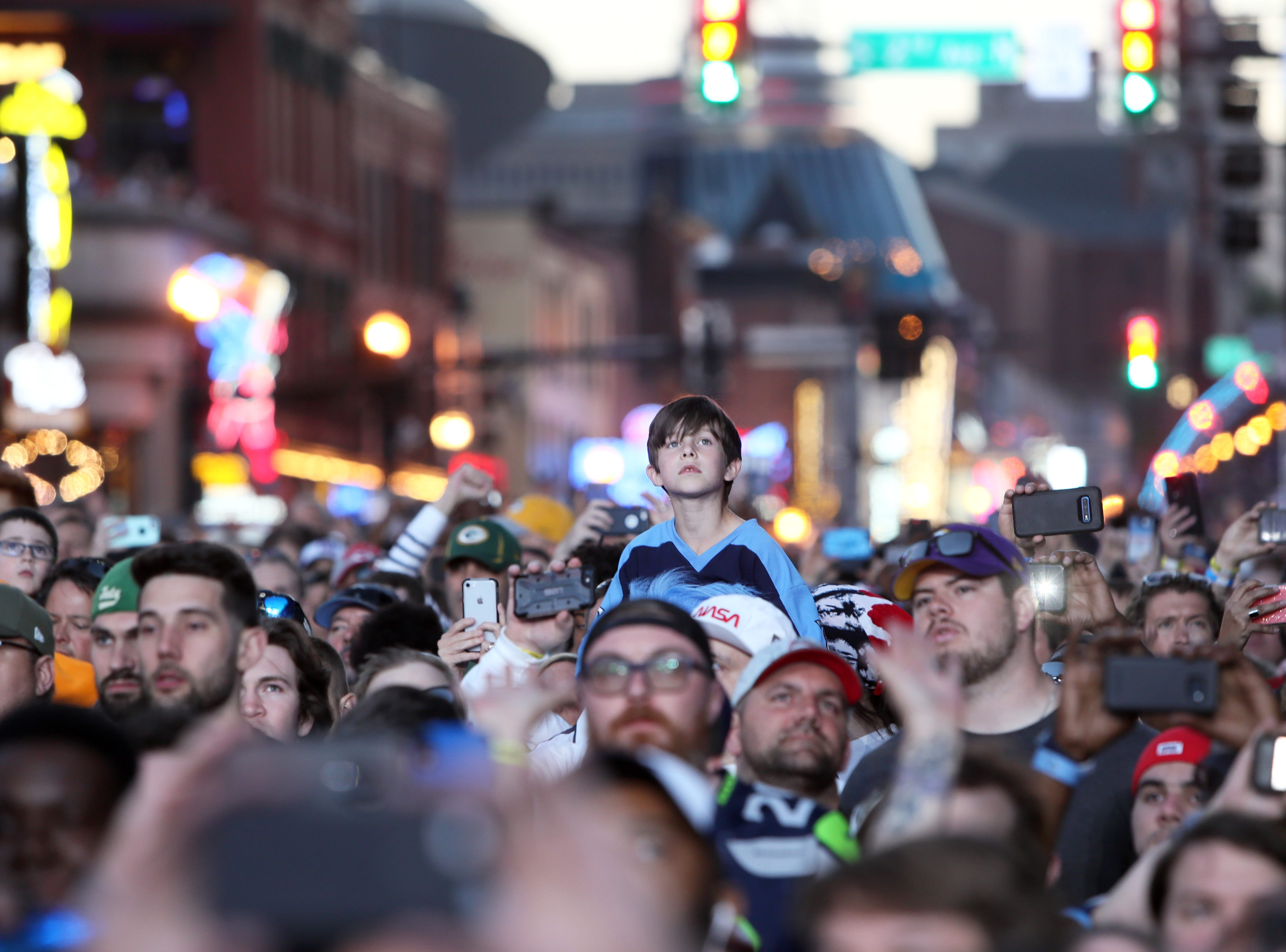 Fans watch as the selection show continues on the NFL draft's second night on Lower Broadway in downtown Nashville on Friday, April 26, 2019.
