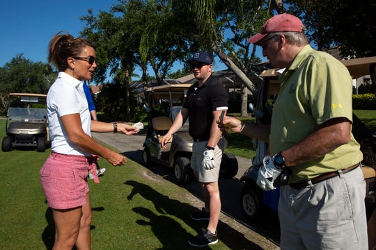 Folds of Honor volunteer Trish Cooke, collects $5 dollar donations from Jim Hawkins, center, and his dad Jim Hawkins, both from Boston, Massachusetts, to participate in the Folds of Honor Day's circle contest, Saturday, April 27, 2019, at the Arrowhead Golf Club in North Naples.