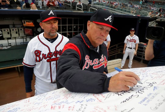 Atlanta Braves manager Brian Snitker, right, signs a get well card for former Braves manager Bobby Cox who reportedly is being hospitalized after suffering a stroke Thursday, April 4, 2019, in Atlanta. Bench coach and former Braves infielder Walt Weiss looks on.